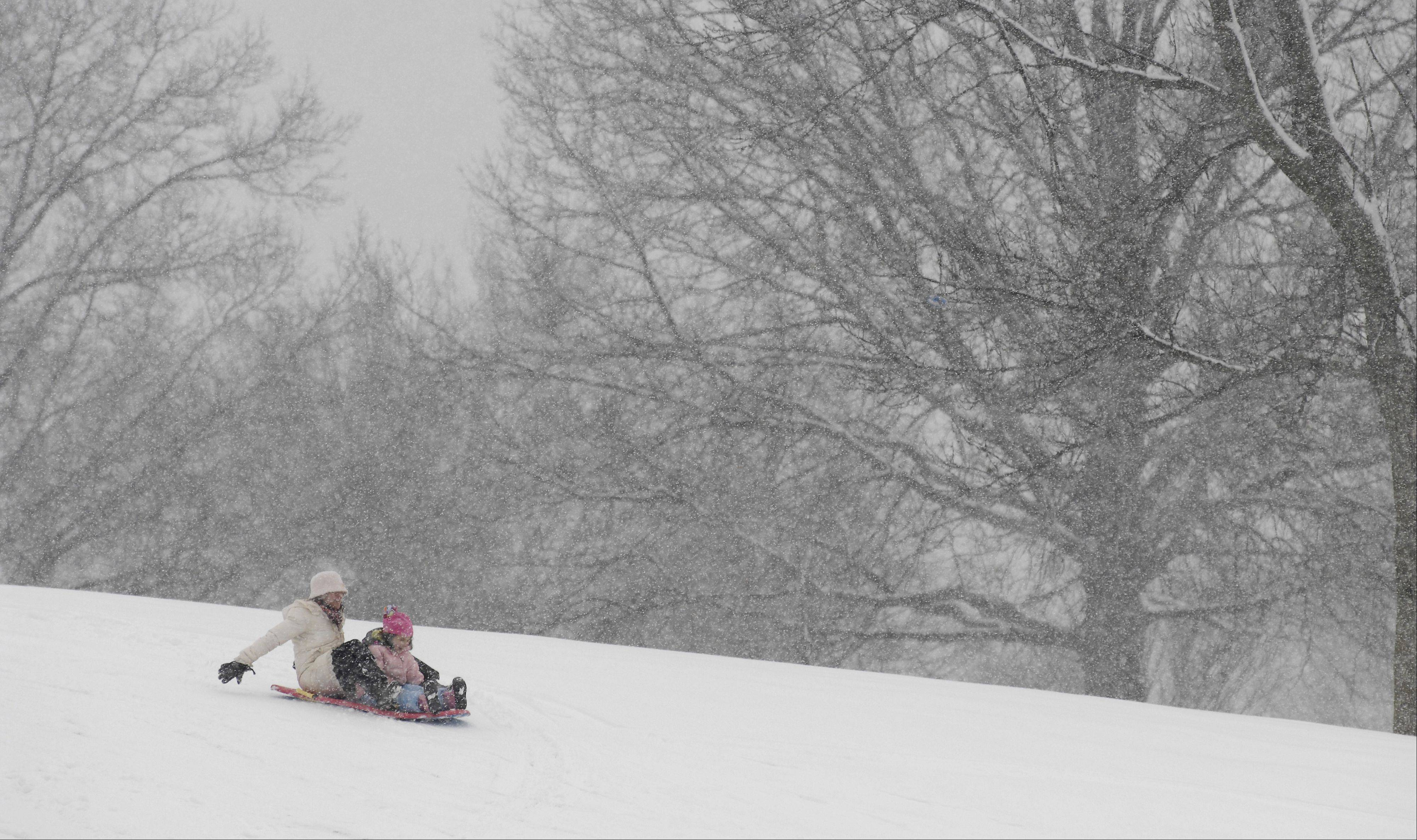 Lynell Iannicelli and her daughter Julie, 5, sled at Newton Park in Glen Ellyn on Tuesday.