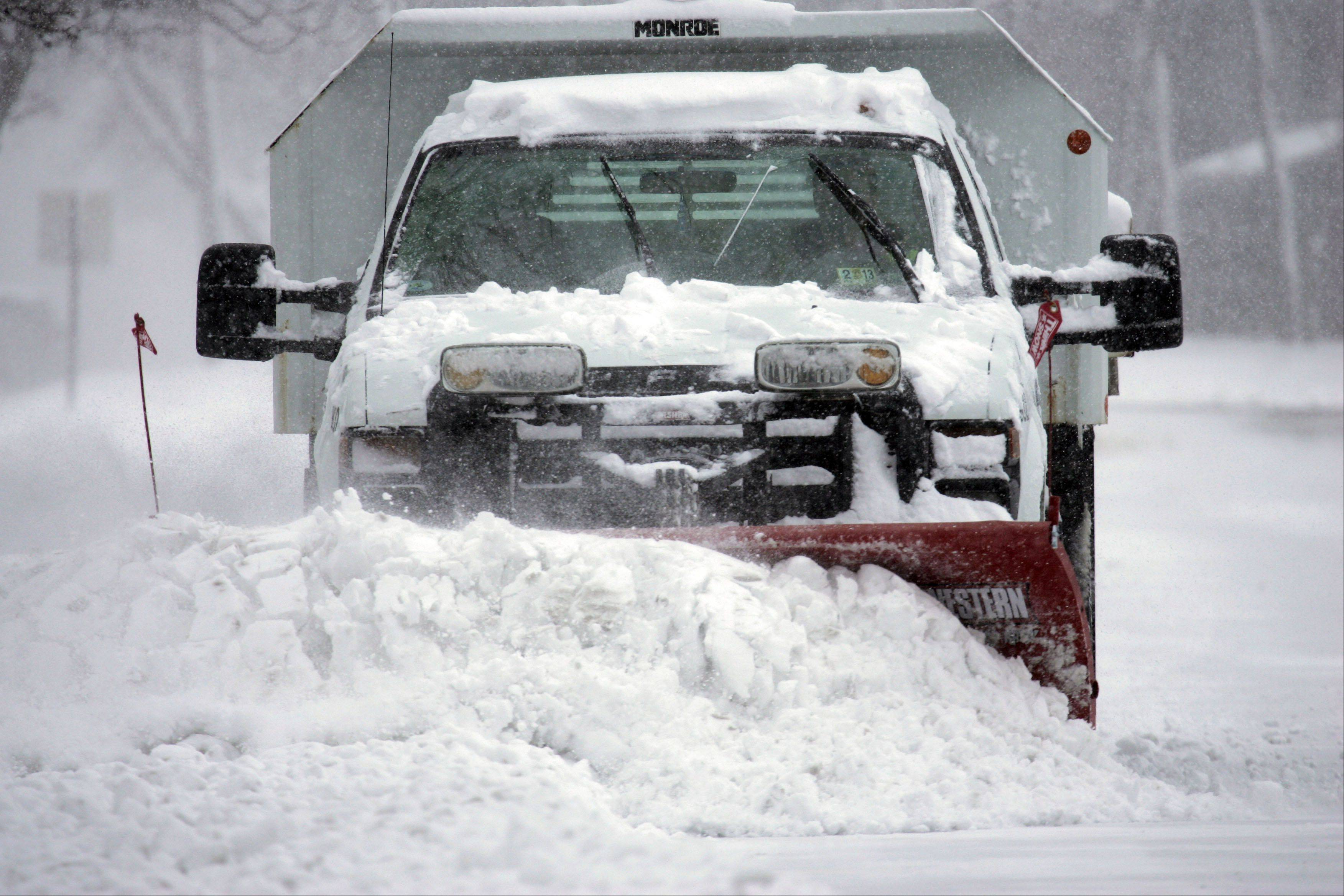 A plow pushes snow one of the Wing Park parking lots Tuesday.