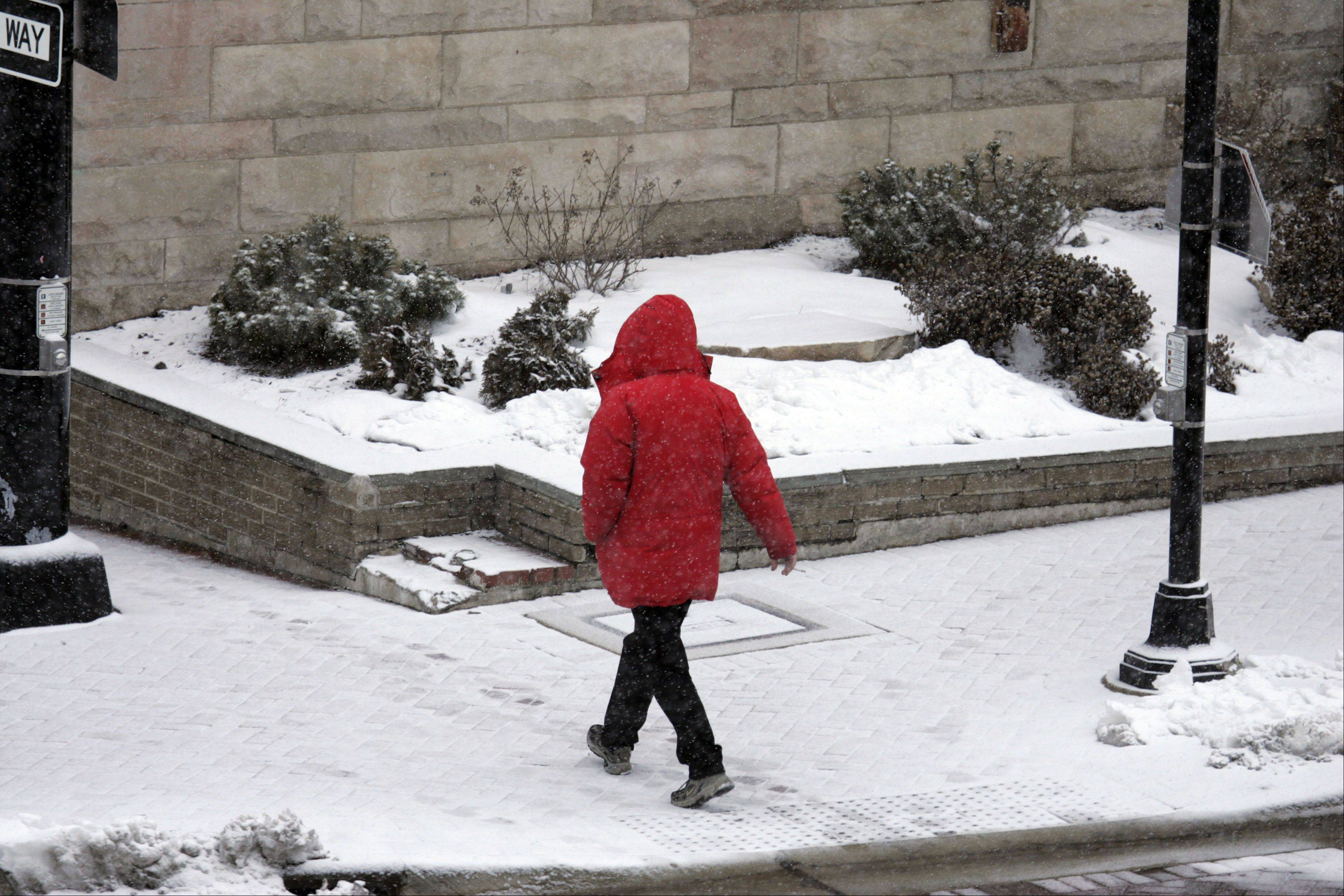 An unidentified person heads West along Highland Ave as a small dusting of snow covers the Elgin area.