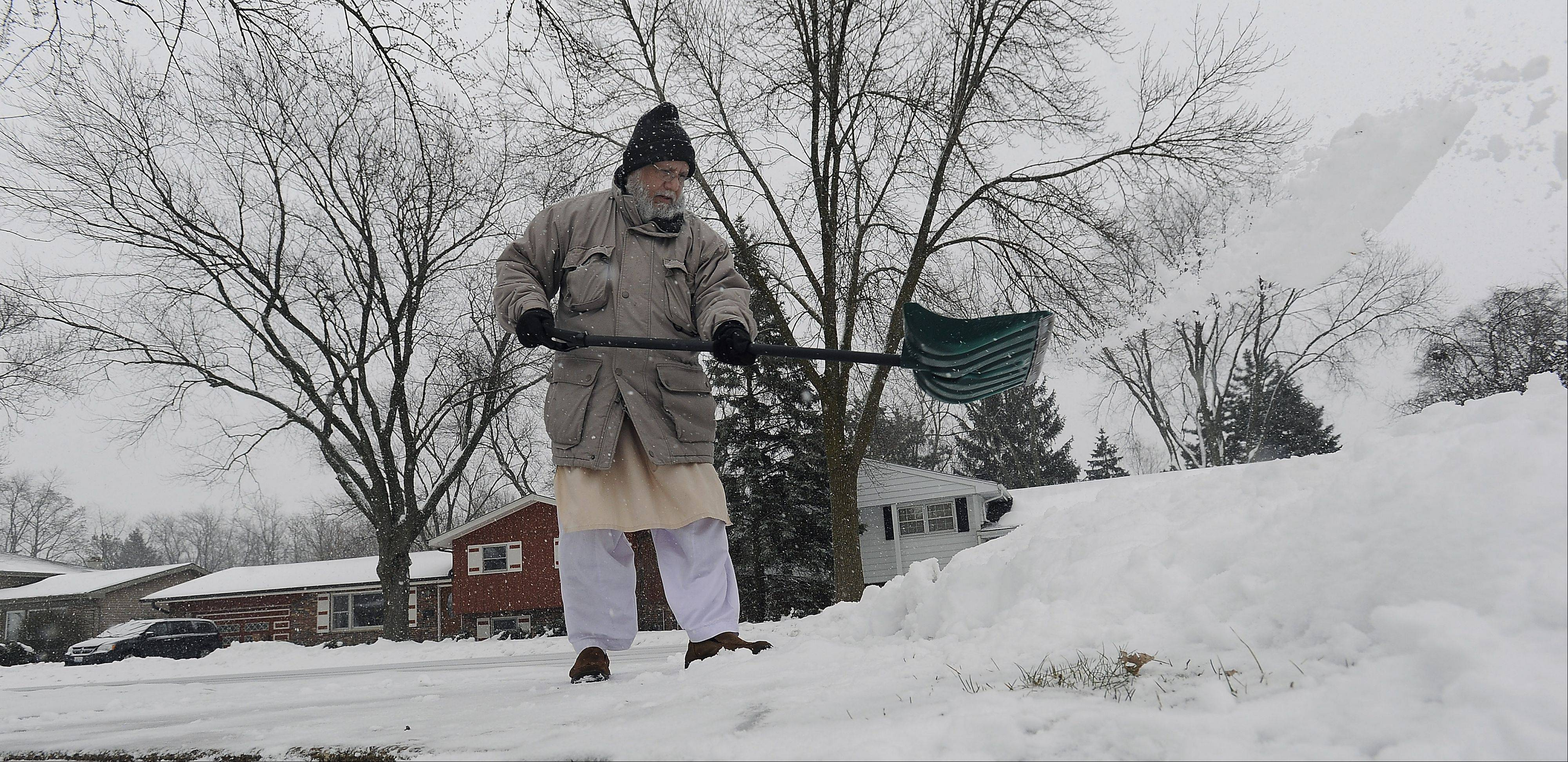 Syed Ahmed of Palatine shovels his driveway while trying to stay ahead of Tuesday's snow.