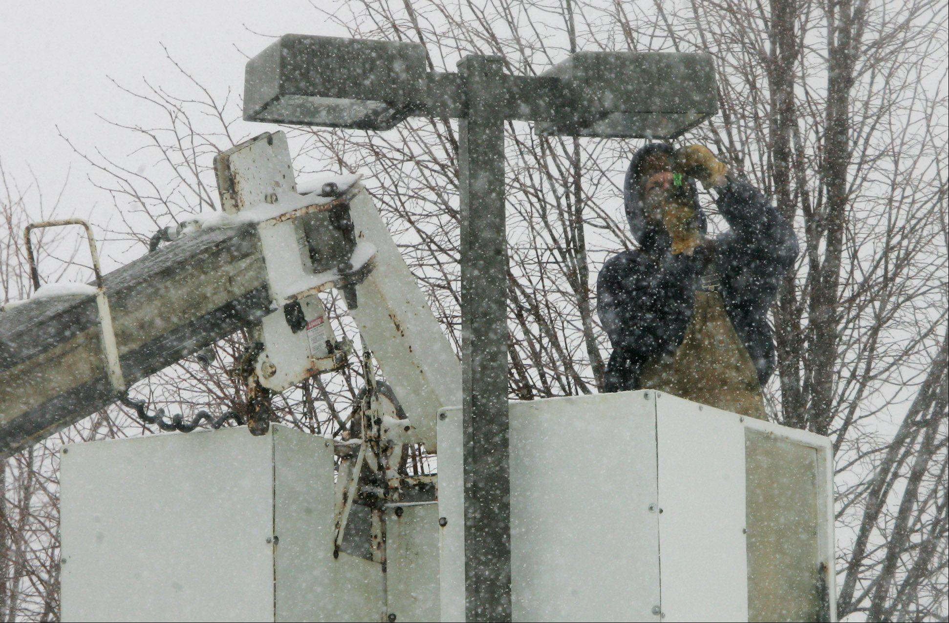 Electrician Matt Funderburk, of Kelso Burnett Co., repairs and replaces lights in the parking lot of St. Mark Lutheran Church in Lindenhurst as snow falls Tuesday in Lake County. The winter snow caused schools and some businesses to close for the day.