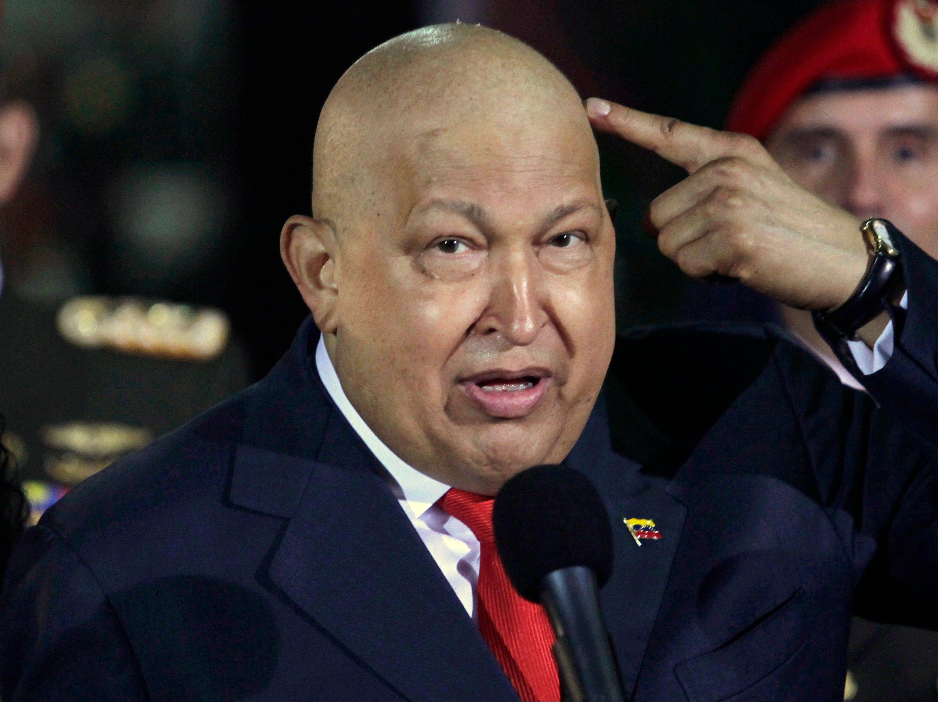 In this Oct. 11, 2011, photo, Venezuela's President Hugo Chavez points at his head to show his hair has started to grow back after his last round of chemotherapy at Miraflores presidential palace in Caracas, Venezuela. Chavez was reported to have died Tuesday.