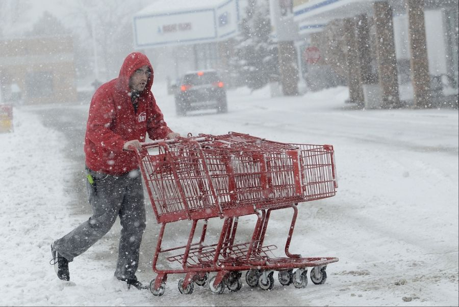 Marcus Ramirez, of Trader Joe's in Lake Zurich, retrieves some shopping carts before they get buried.