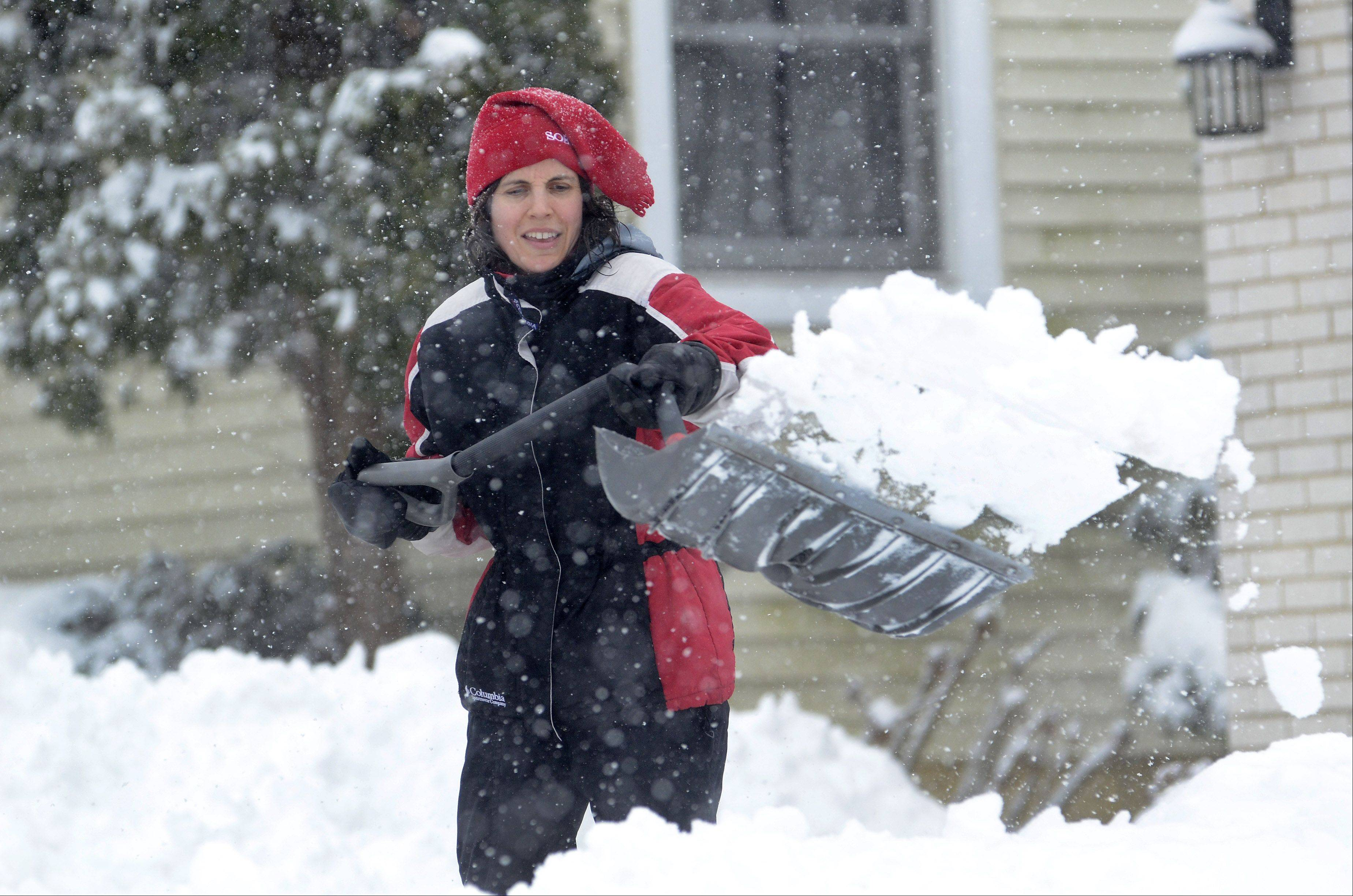 Jamie Hills of Lake Zurich shovels out her driveway on Prairie Lane.