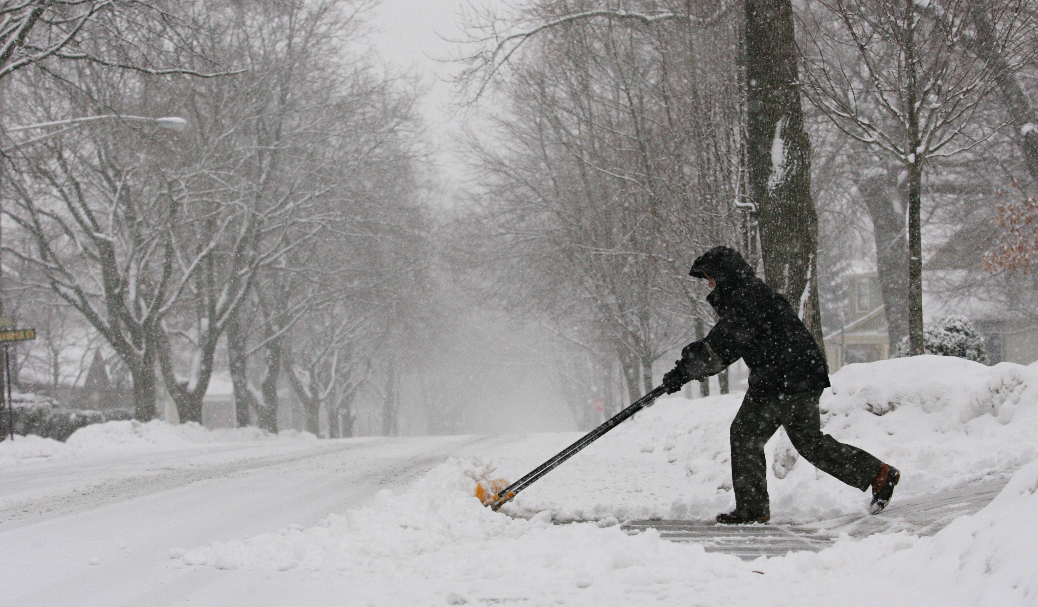 Jay Guevara of West Dundee pushes snow from his driveway into the street Tuesday morning, clearing a path to get out to work.
