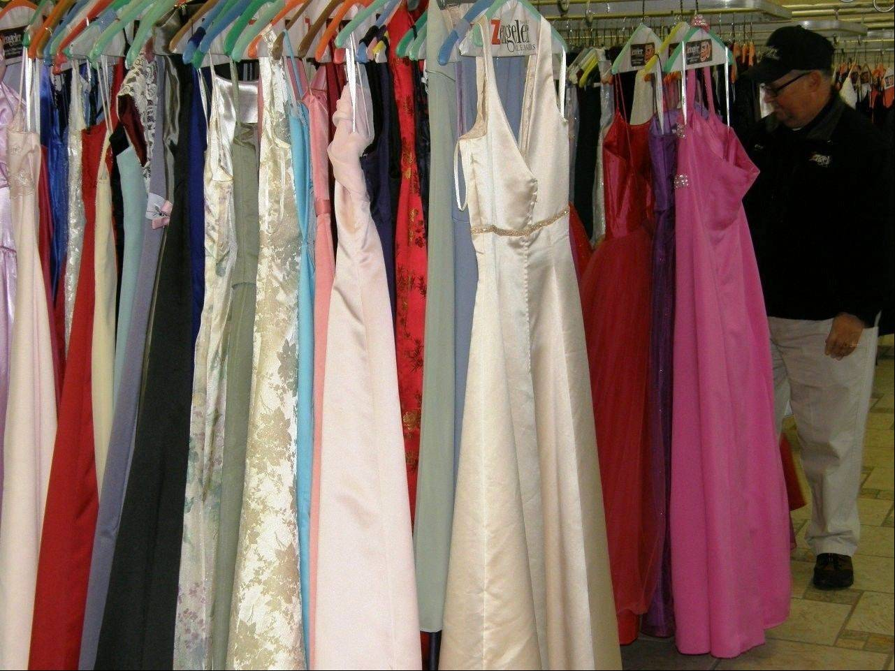 Zengeler Cleaners Route Supervisor Pete Donis inspects dresses prior to a delivery to the Glass Slipper Project for a previous year's collection drive.