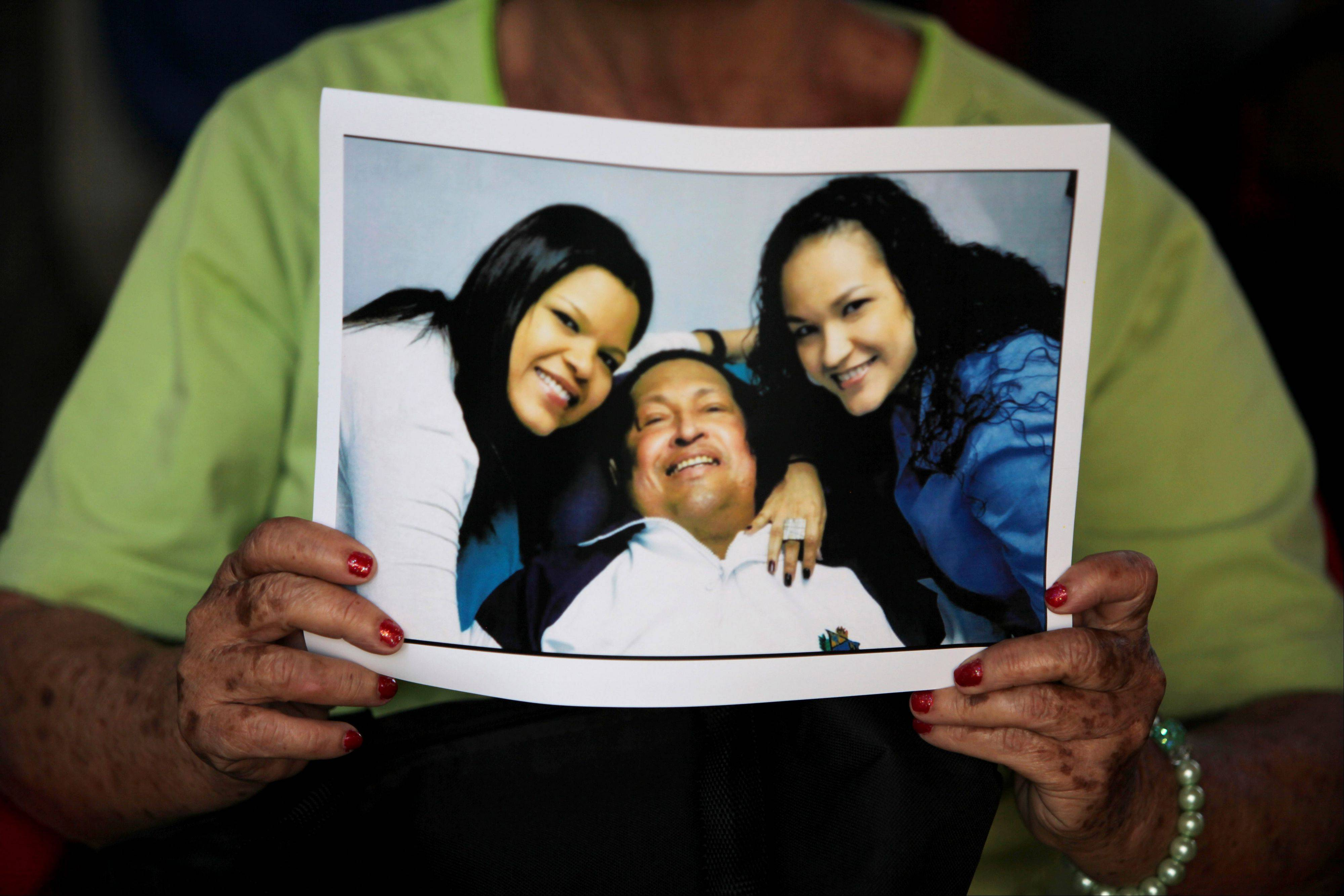 "A woman holds a purchased copy of a photo showing Venezuela's President Hugo Chavez at the hospital in Havana, with two of his daughters. Venezuela's government said that President Hugo Chavez's respiratory problems have gotten worse and that the ailing leader is in ""very delicate"" condition. Communications Minister Ernesto Villegas said late Monday March 4, 2013 in a statement read on national television that Chavez has a ""severe infection."" The 58-year-old Chavez first revealed an unspecified cancer in the pelvic region in June 2011, and reported undergoing radiation treatment and chemotherapy after earlier operations. He underwent cancer surgery in Cuba on Dec. 11 and flew back to Caracas on Feb. 18."
