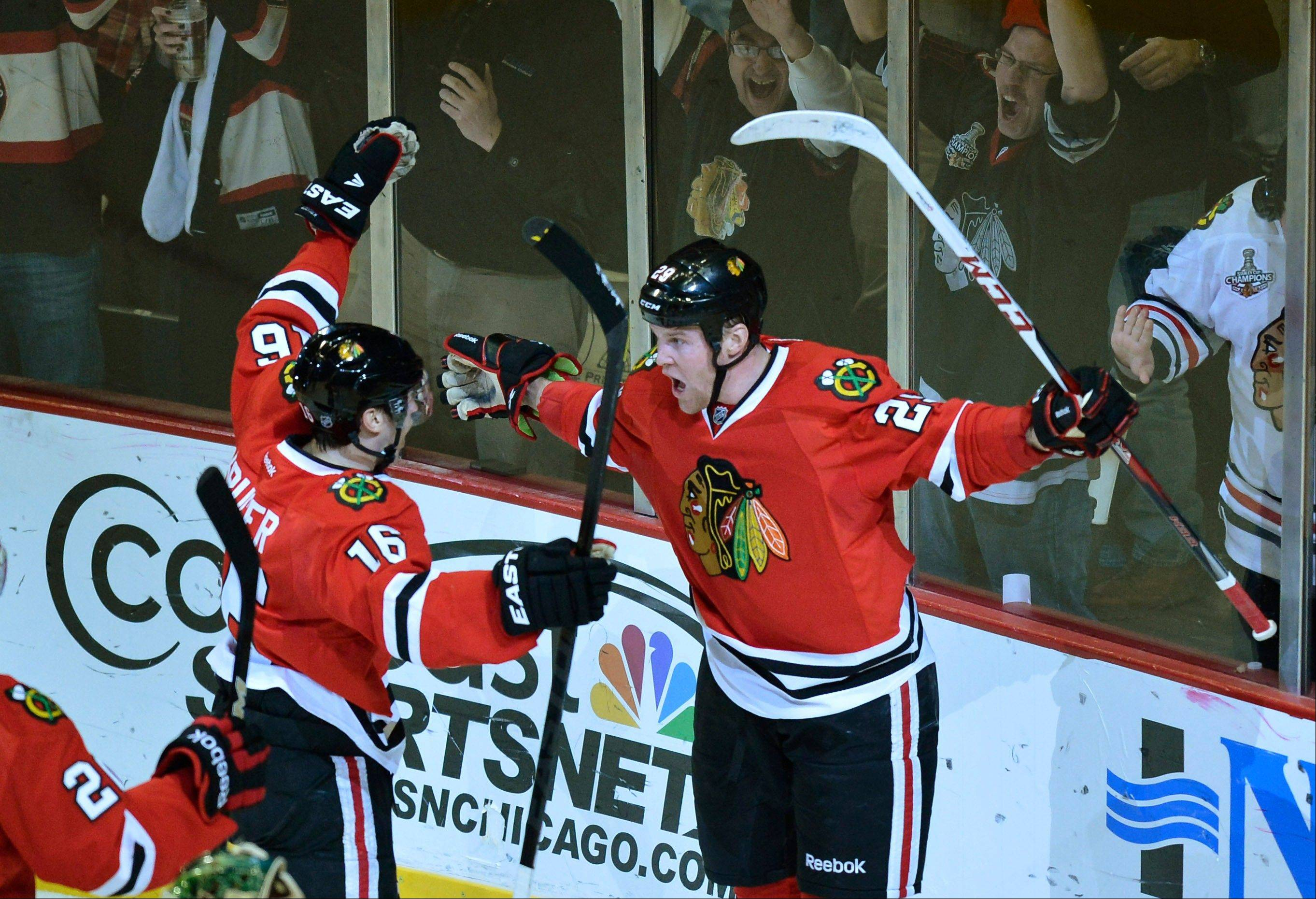 Blackhawks center Marcus Kruger, left, and left wing Bryan Bickell celebrate after Bickell scored during the first period of an NHL hockey game against the Minnesota Wild, Tuesday, March 5, 2013 in Chicago.