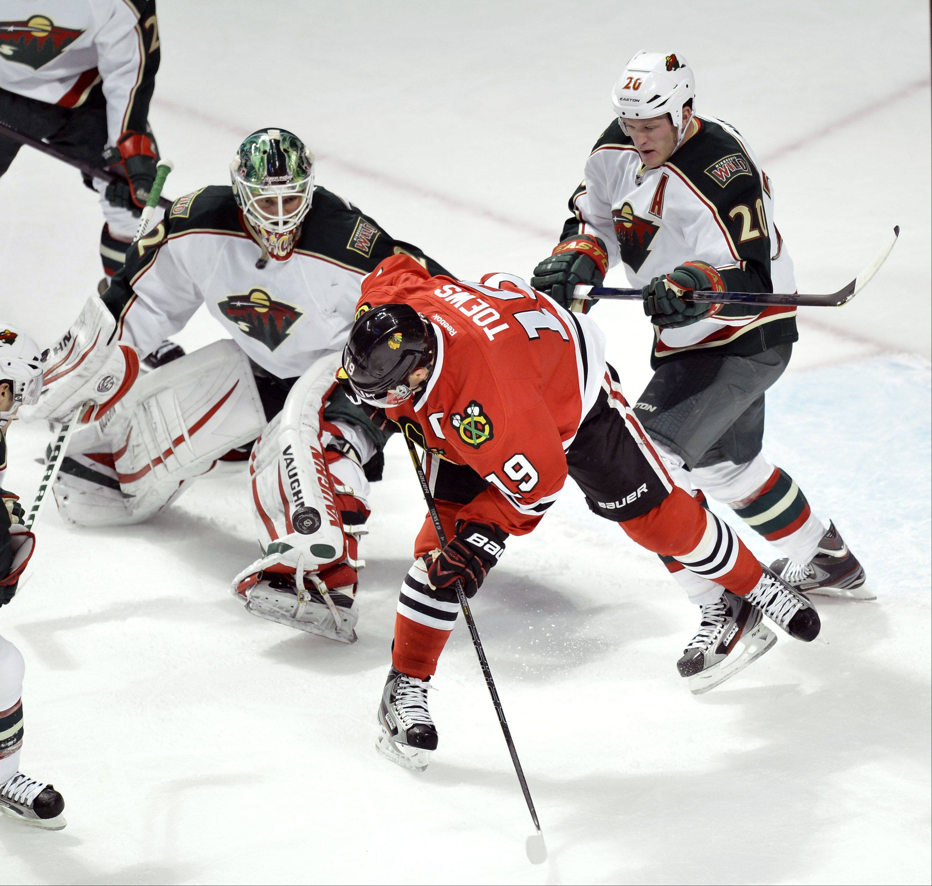 Chicago Blackhawks center Jonathan Toews, center, tries to score as Minnesota Wild goalie Niklas Backstrom of Finland, left, and defenseman Ryan Suter defend during the first period.