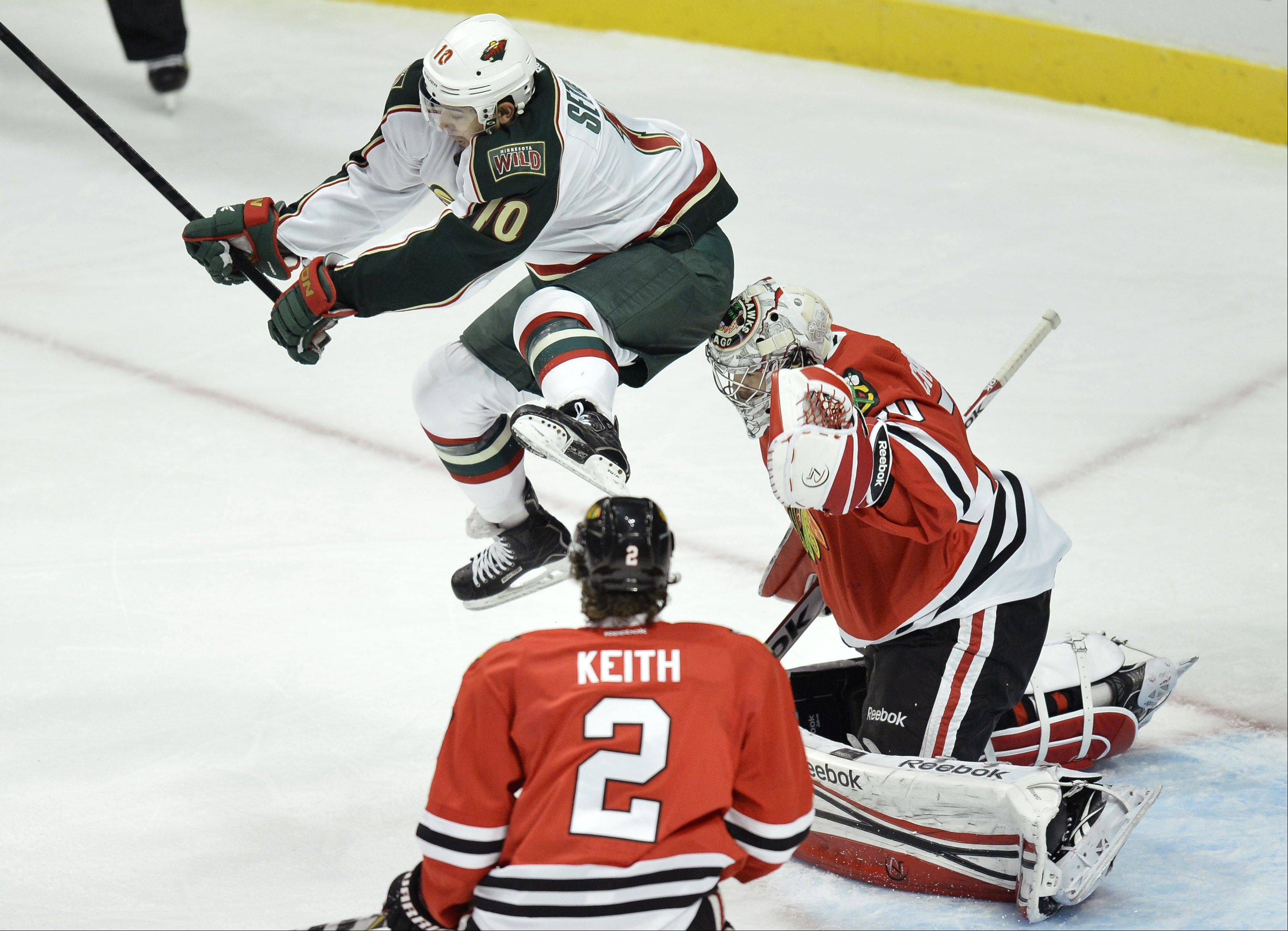 Minnesota Wild right wing Devin Setoguchi , left, leaps into the air to avoid a shot on Chicago Blackhawks goalie Corey Crawford, right, during the first period.