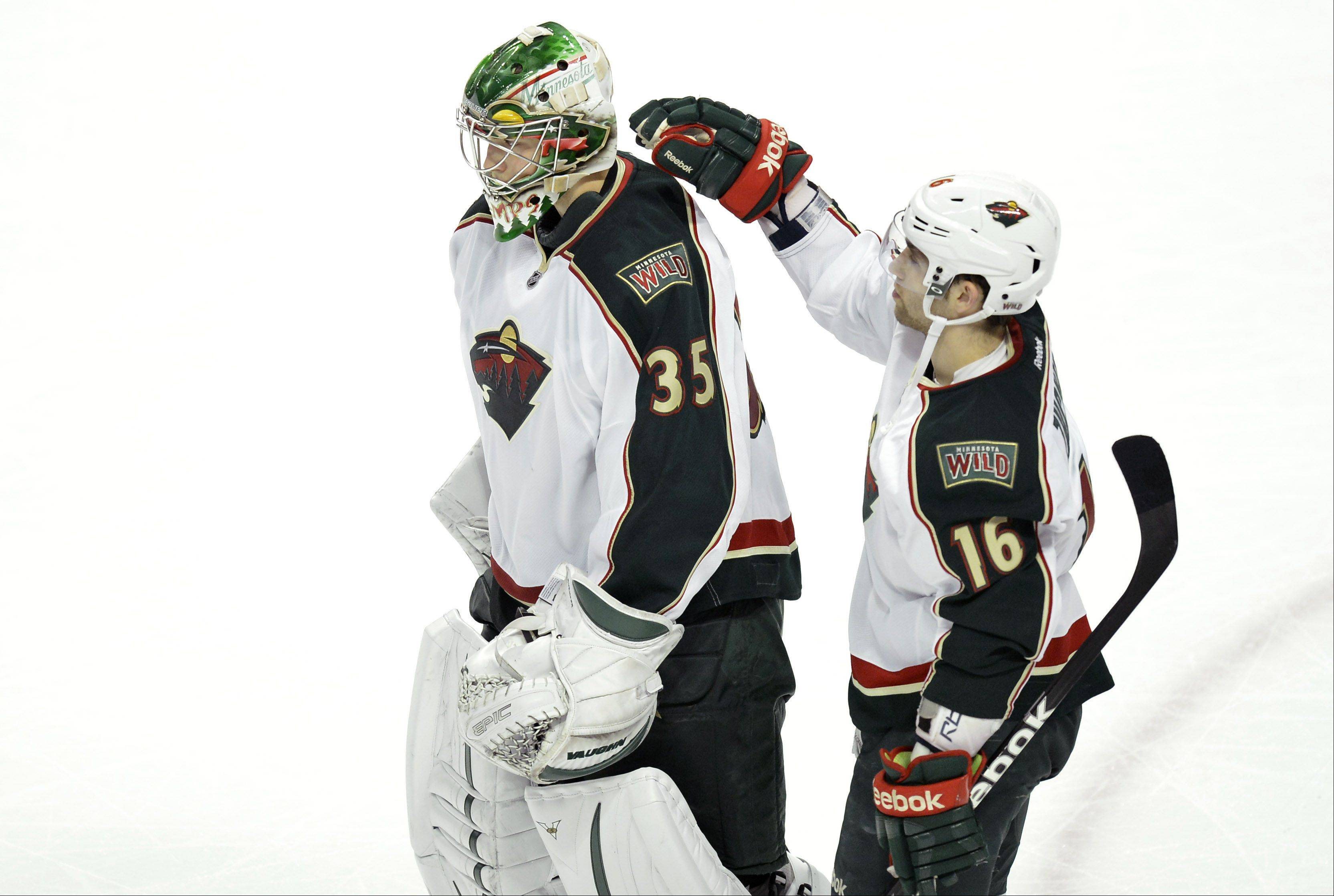Minnesota Wild left wing Jason Zucker, left, pats goalie Darcy Kuemper on the back after they lost to the Chicago Blackhawks.