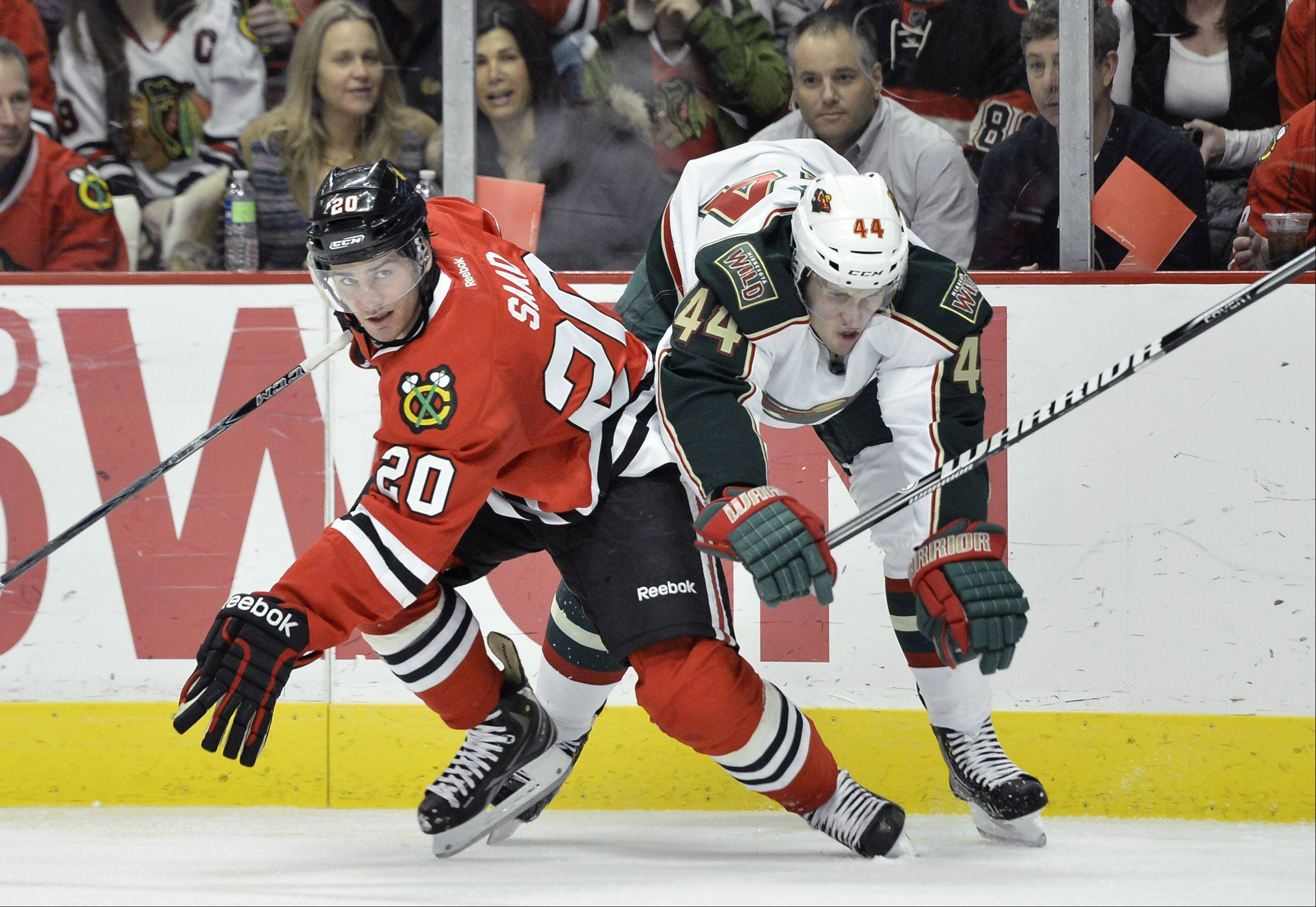 Chicago Blackhawks left wing Brandon Saad, left, checks Minnesota Wild defenseman Justin Falk during the second period .