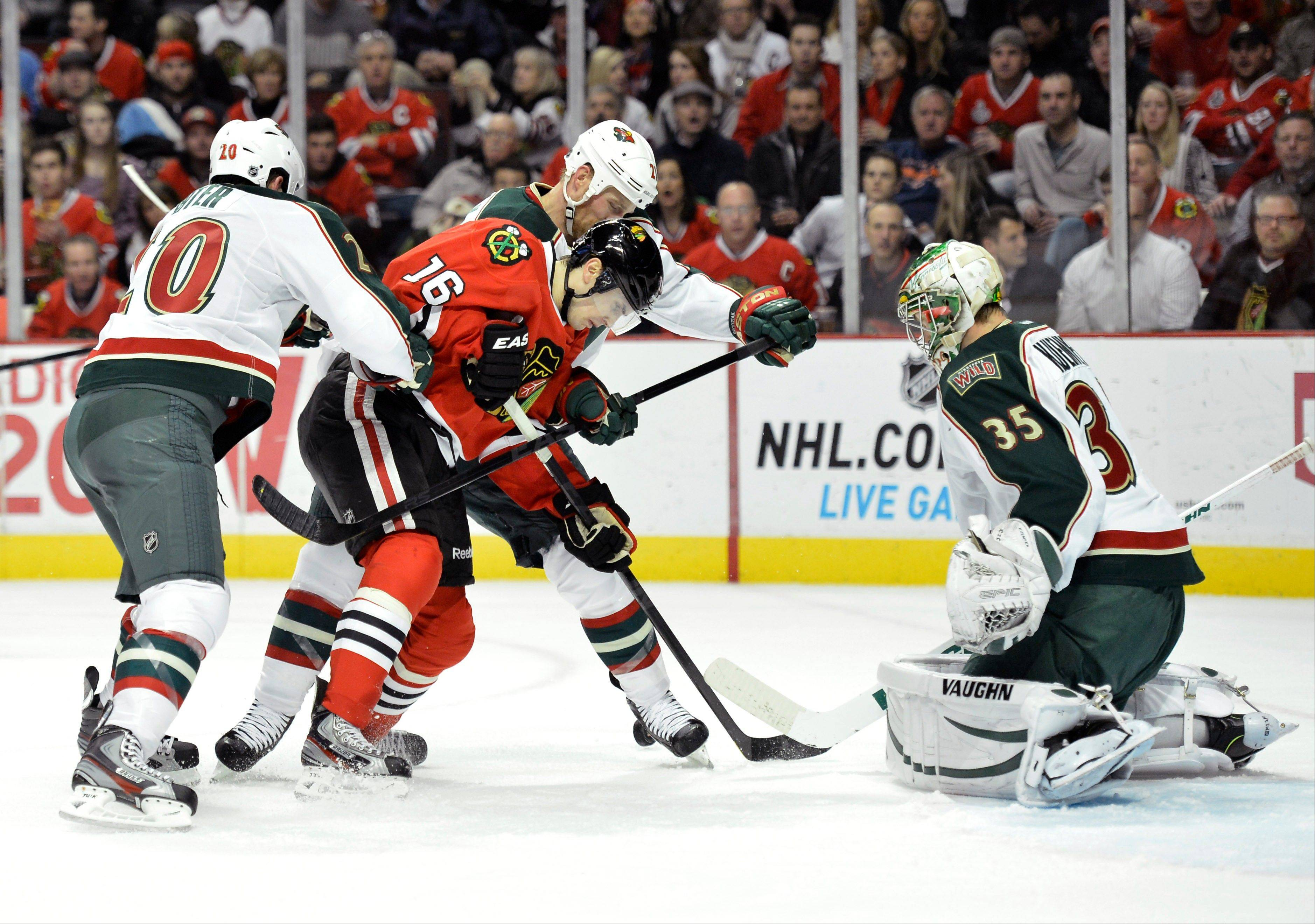 Chicago Blackhawks center Marcus Kruger of Sweden tries to score as Minnesota Wild defenseman Ryan Suter, left to right, center Kyle Brodziak and goalie Darcy Kuemper defend during the second period .