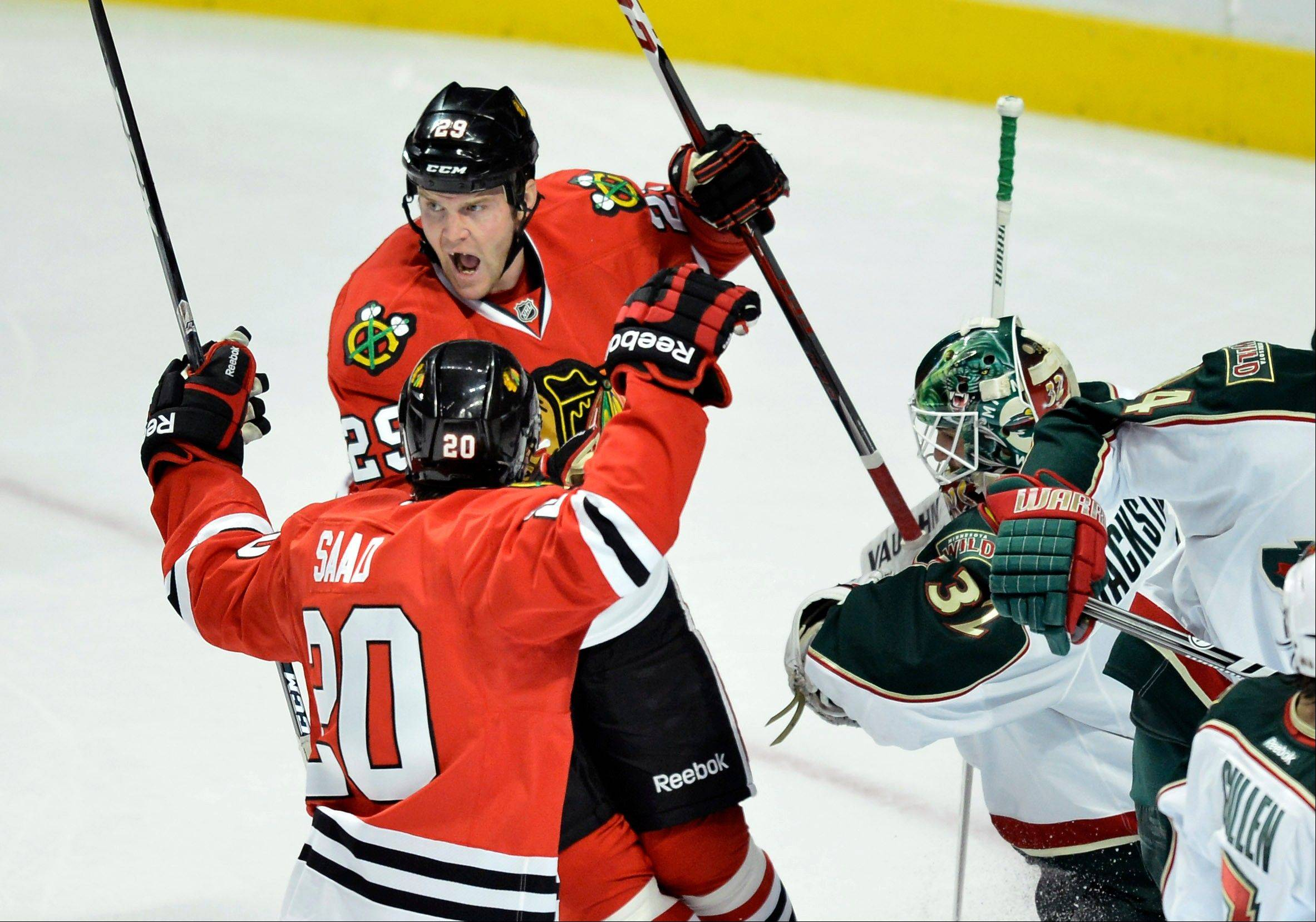 Chicago Blackhawks wingers Bryan Bickell and Brandon Saad, left, celebrate after Bickell scored past Minnesota Wild goalie Niklas Backstrom, left, during the first period