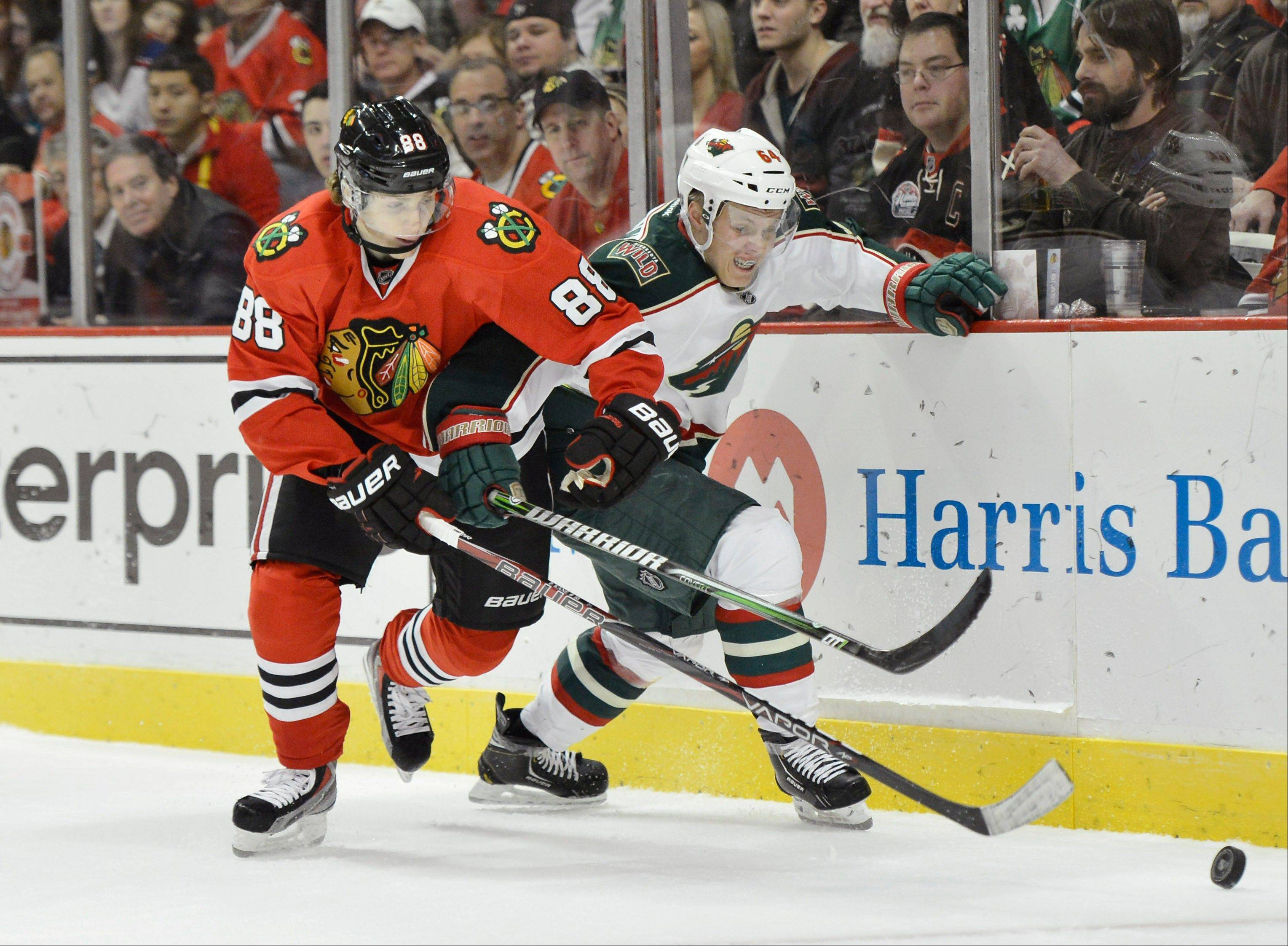Chicago Blackhawks right wing Patrick Kane, left, and Minnesota Wild center Mikael Granlund of Finland go for the puck during the second period.