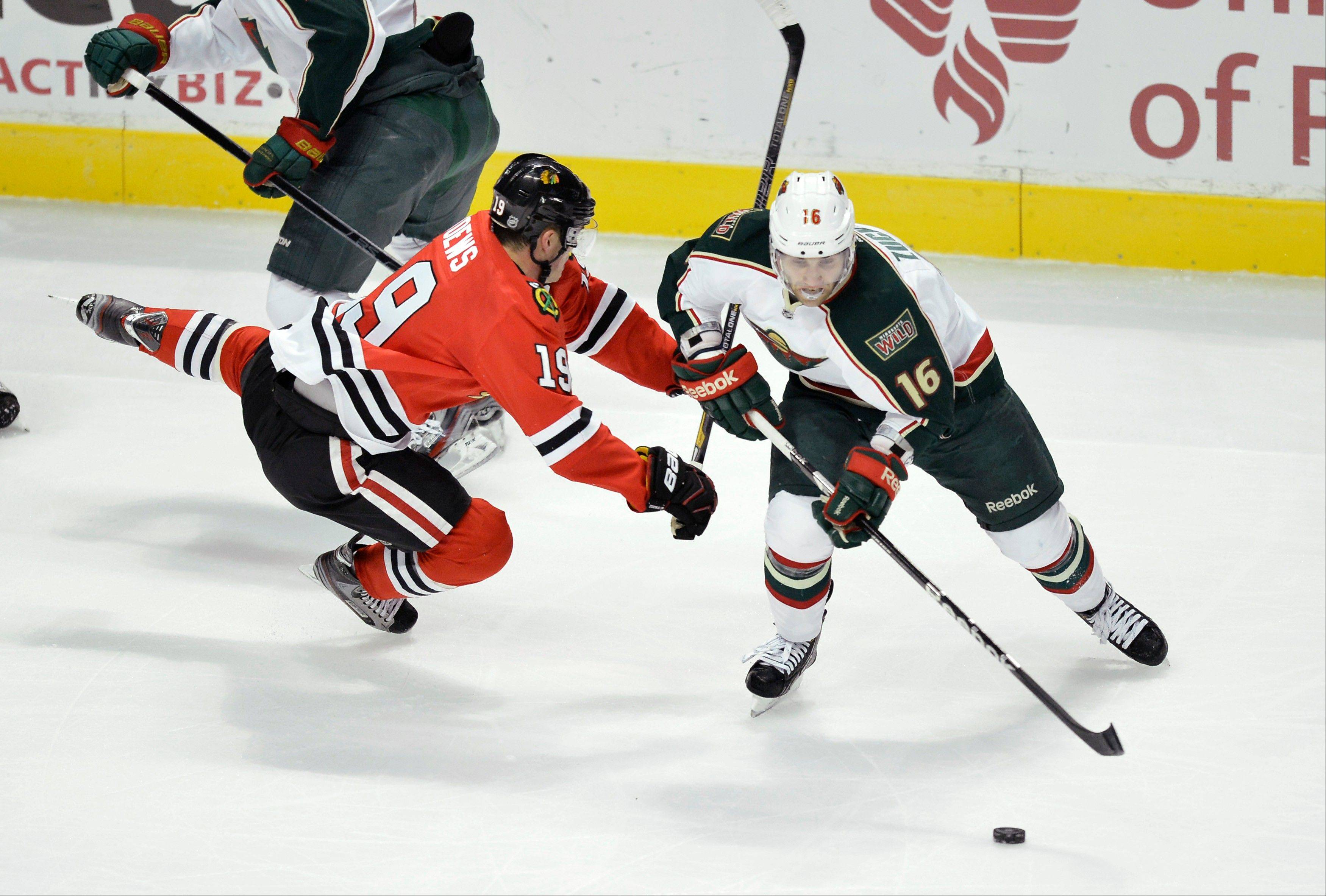 Chicago Blackhawks center Jonathan Toews, left, falls as Minnesota Wild left wing Jason Zucker skates with the puck during the first period.