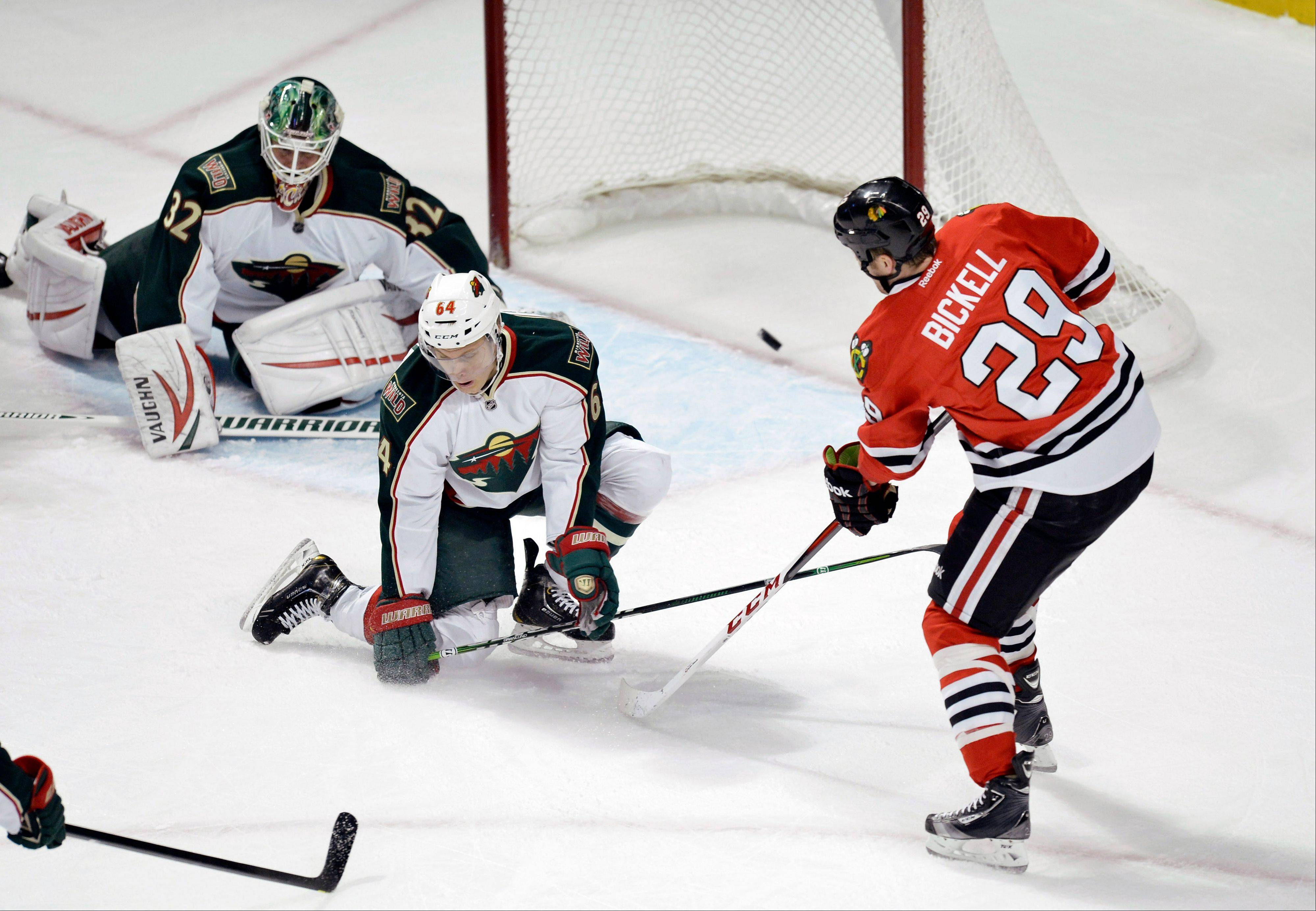 Chicago Blackhawks left wing Bryan Bickell, left to right, scores past Minnesota Wild center Mikael Granlund of Finland, and goalie Niklas Backstrom of Finland during the first period.