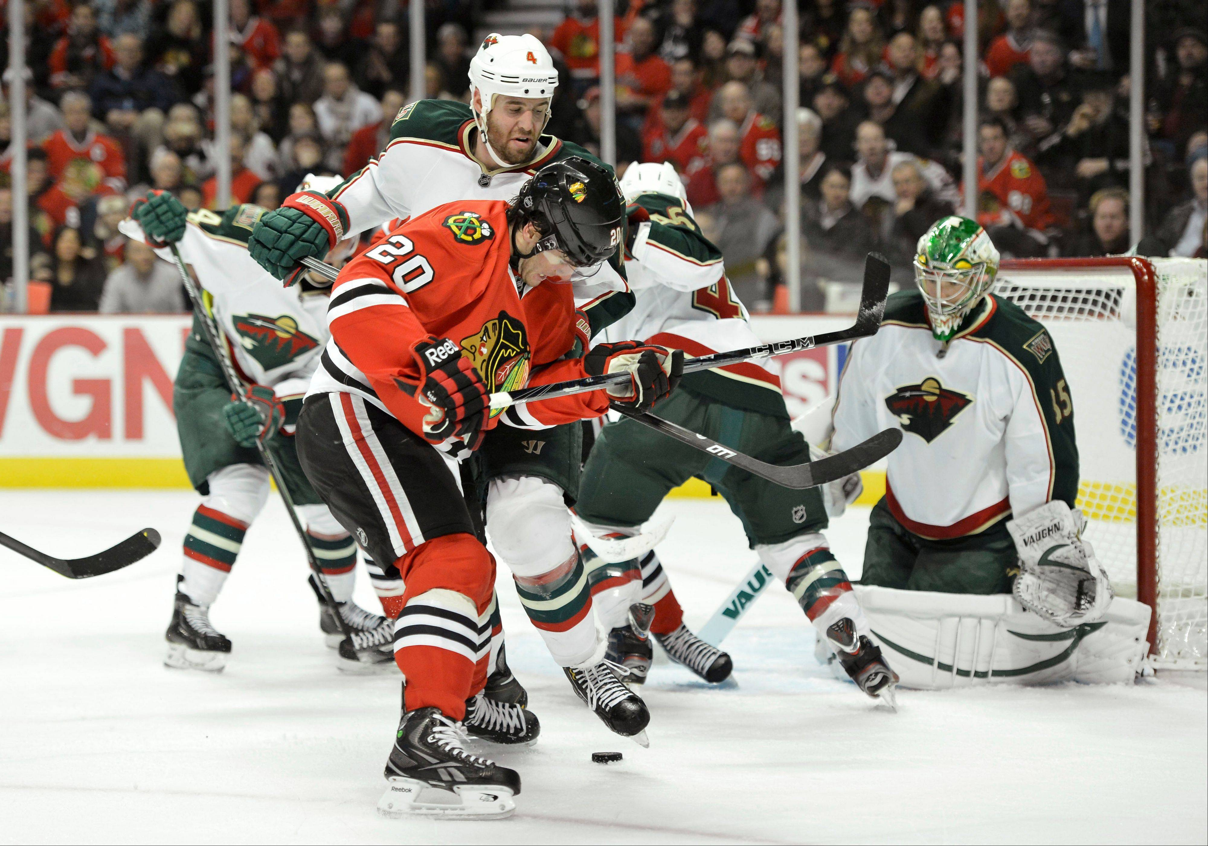 Minnesota Wild defenseman Clayton Stoner, center, pushes Chicago Blackhawks left wing Brandon Saad, left, off the puck during the second period.