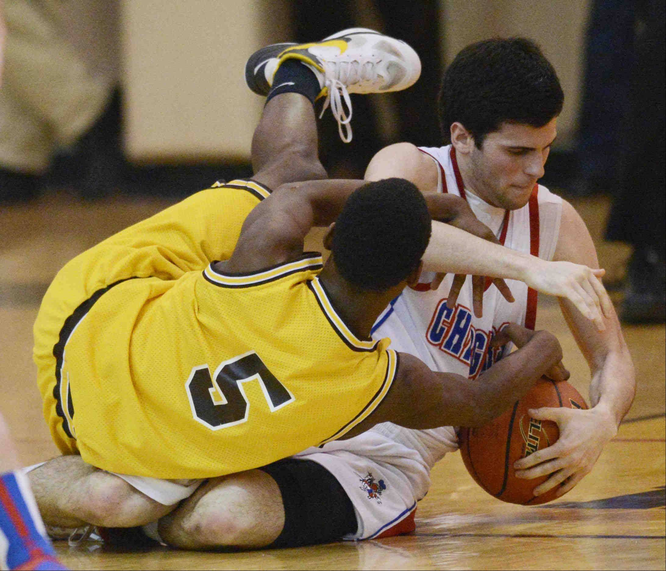 Jacobs' Chrishawn Orange and Dundee-Crown's Trent Muscat tangle on the floor during Wednesday's Jacobs Class 4A regional game in Algonquin.