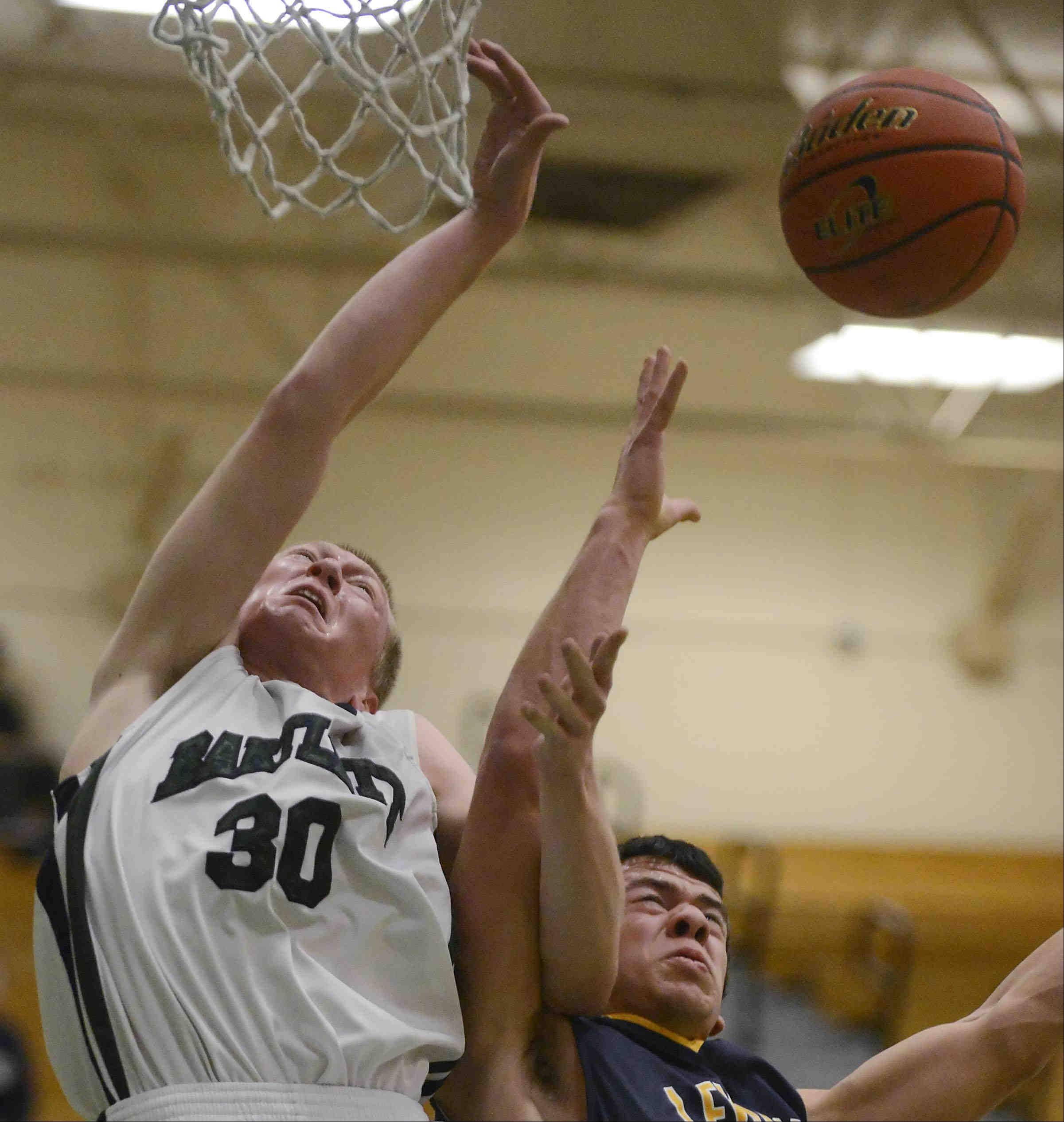 Bartlett's Billy Kramer and Leyden's Nick Best compete for a rebound in Thursday's 4A York regional game in Elmhurst.