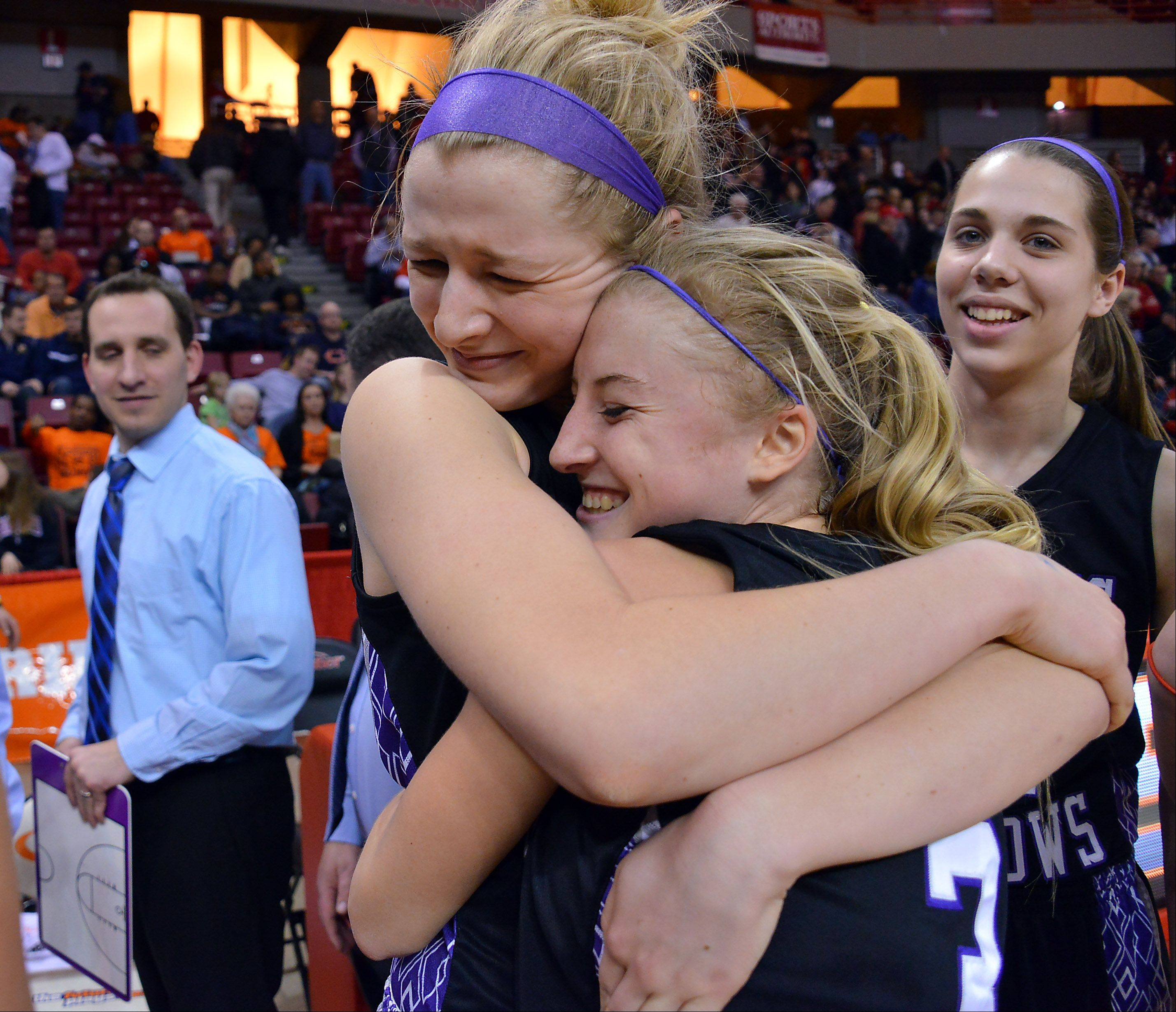 Rolling Meadows' Jackie Kemph is hugged by Jenny Vliet at the end of Friday's Class 4A girls basketball game in Normal.