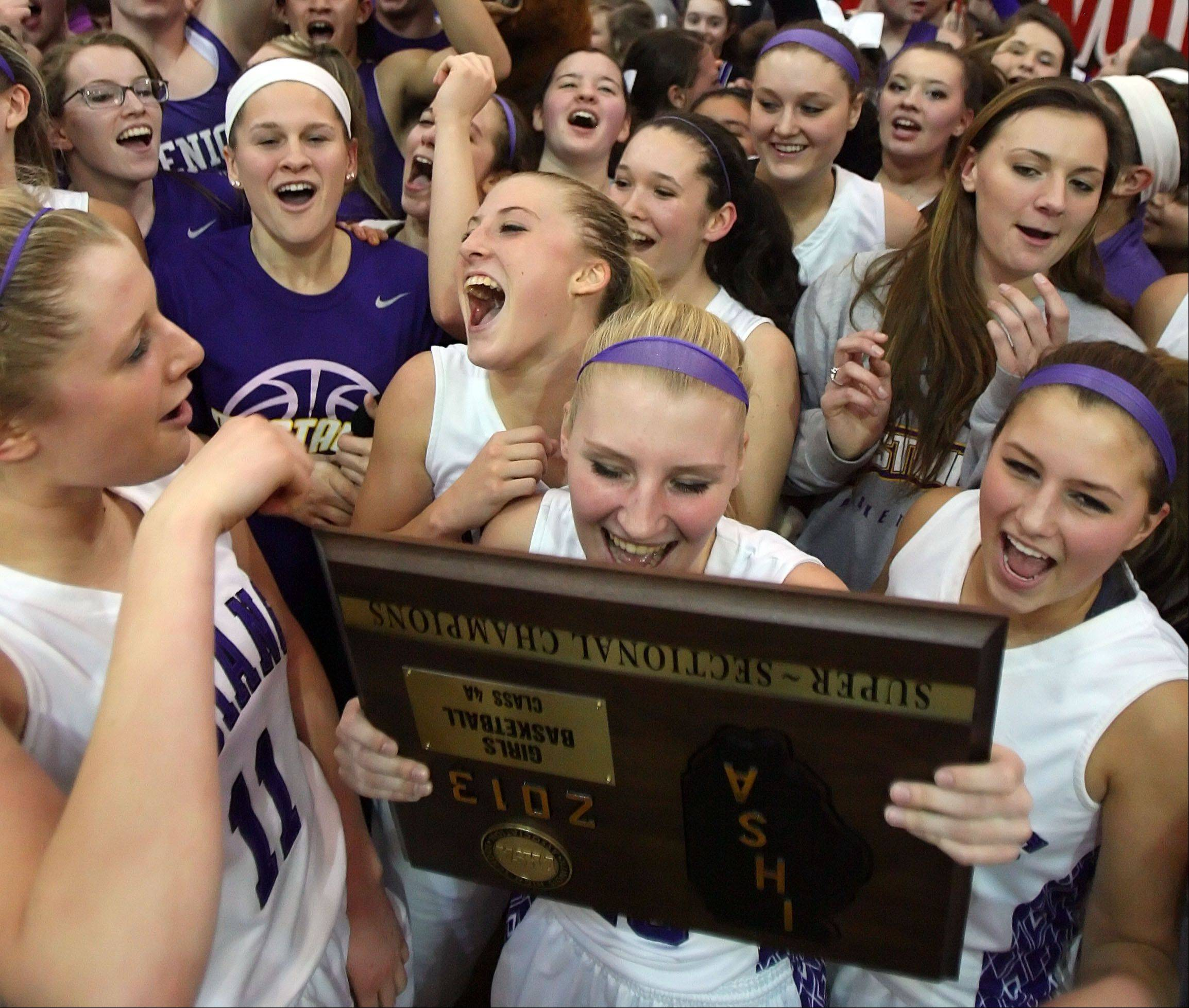 Rolling Meadows' players celebrate with the supersectional trophy after defeating Evanston Monday in Skokie.