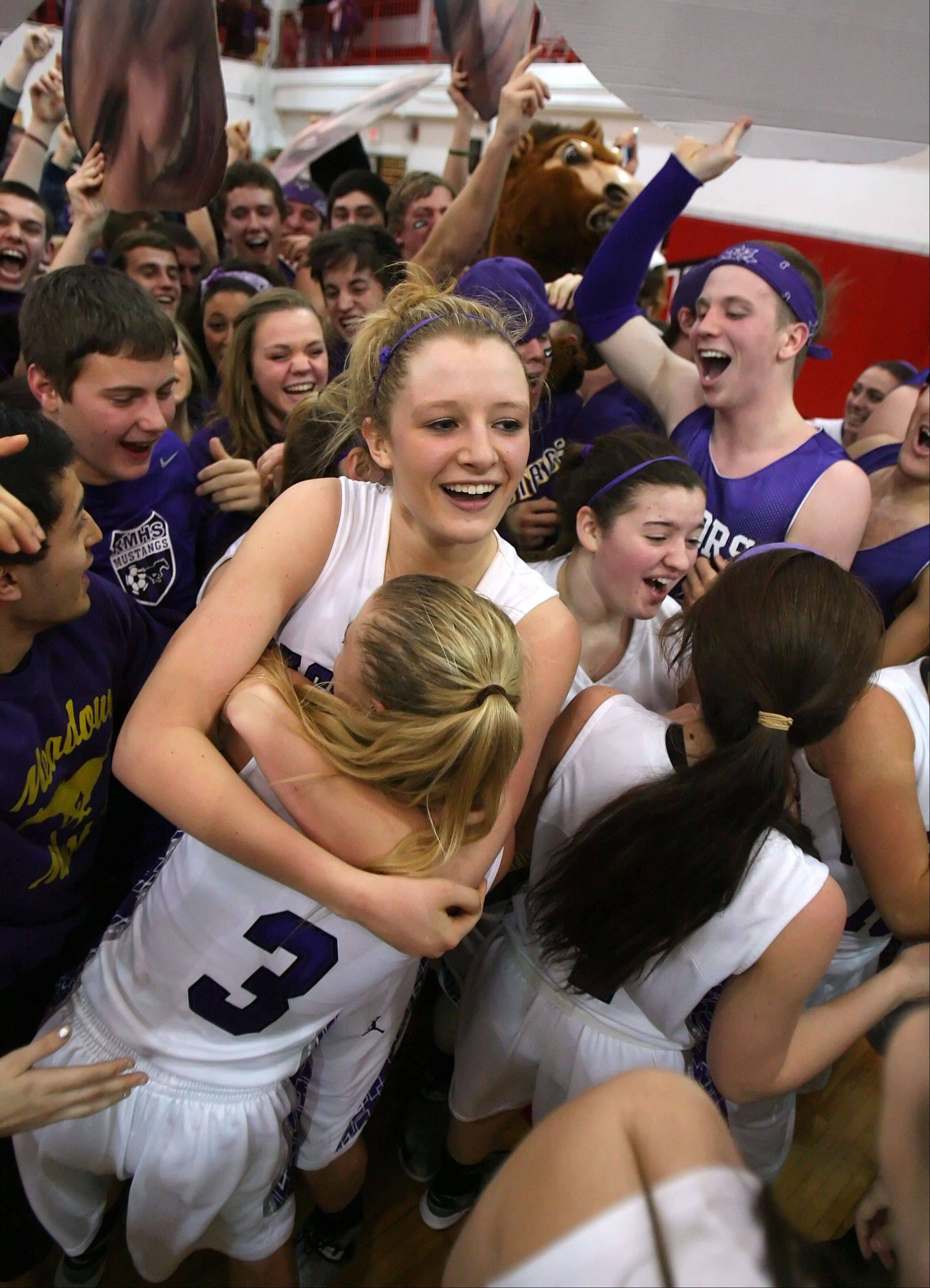 Rolling Meadows' Jenny Vliet and Jackie Kemph celebrate as the fans rush the floor after beating Evanston in Class 4A Niles West supersectional Monday in Skokie.