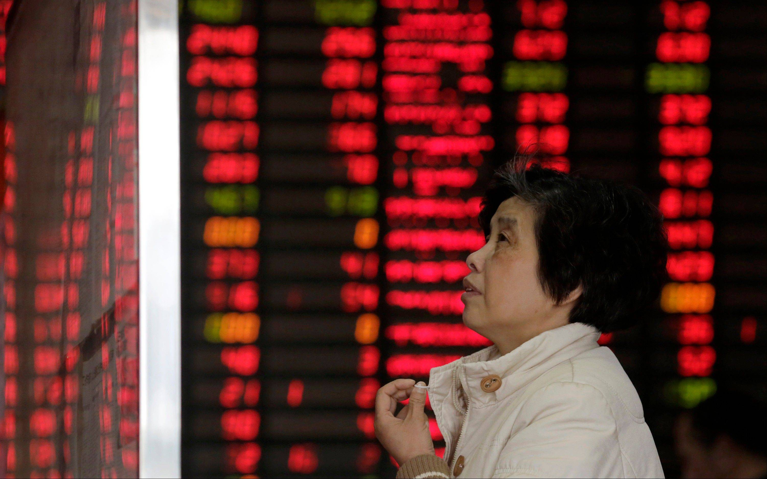 An investor looks at the stock bulletin board at a private securities company on Wednesday.