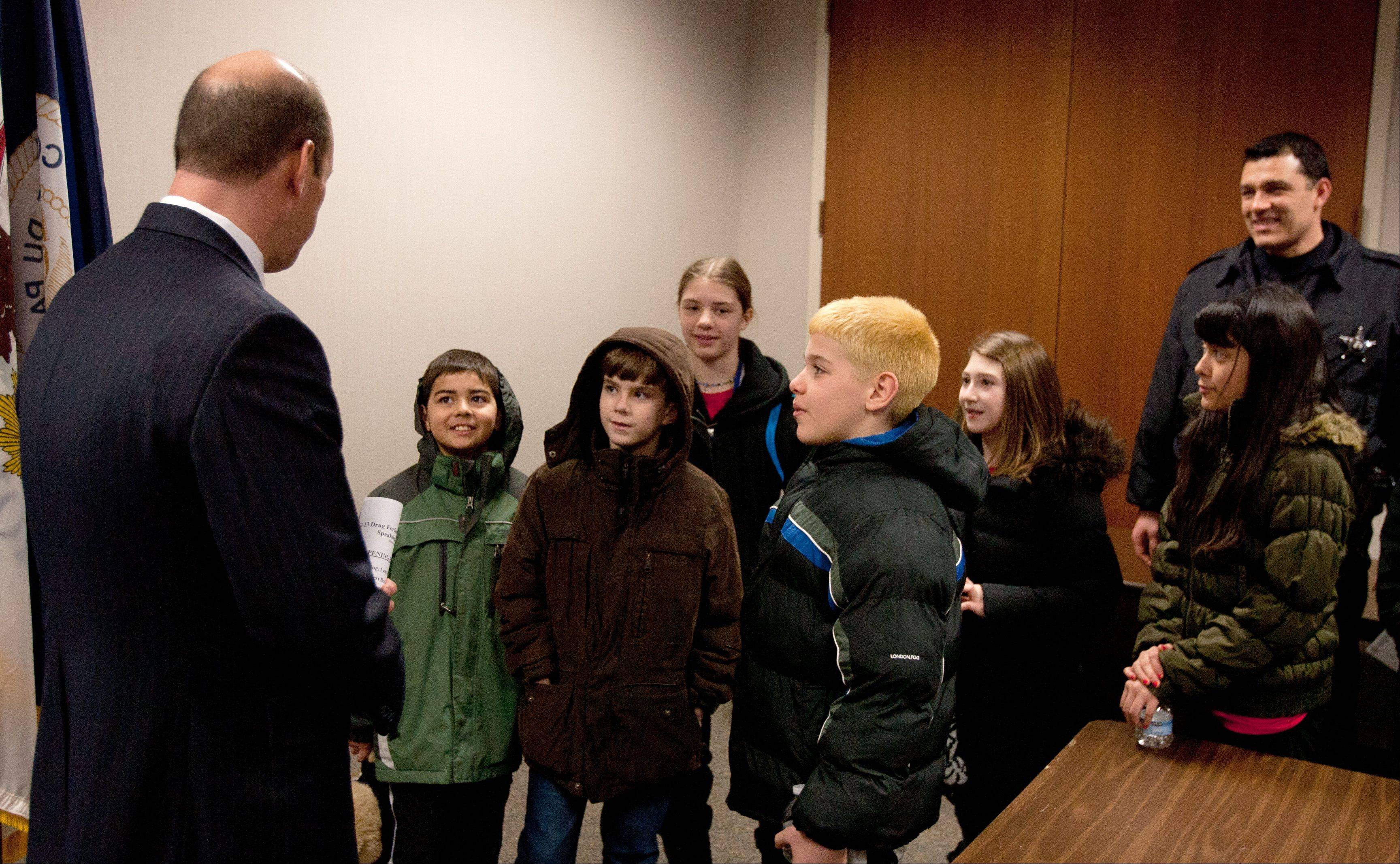 DuPage County State�s Attorney Bob Berlin speaks Wednesday to students from Heritage Lakes School in Carol Stream about avoiding illegal drugs. At right is police officer Pablo Castro.