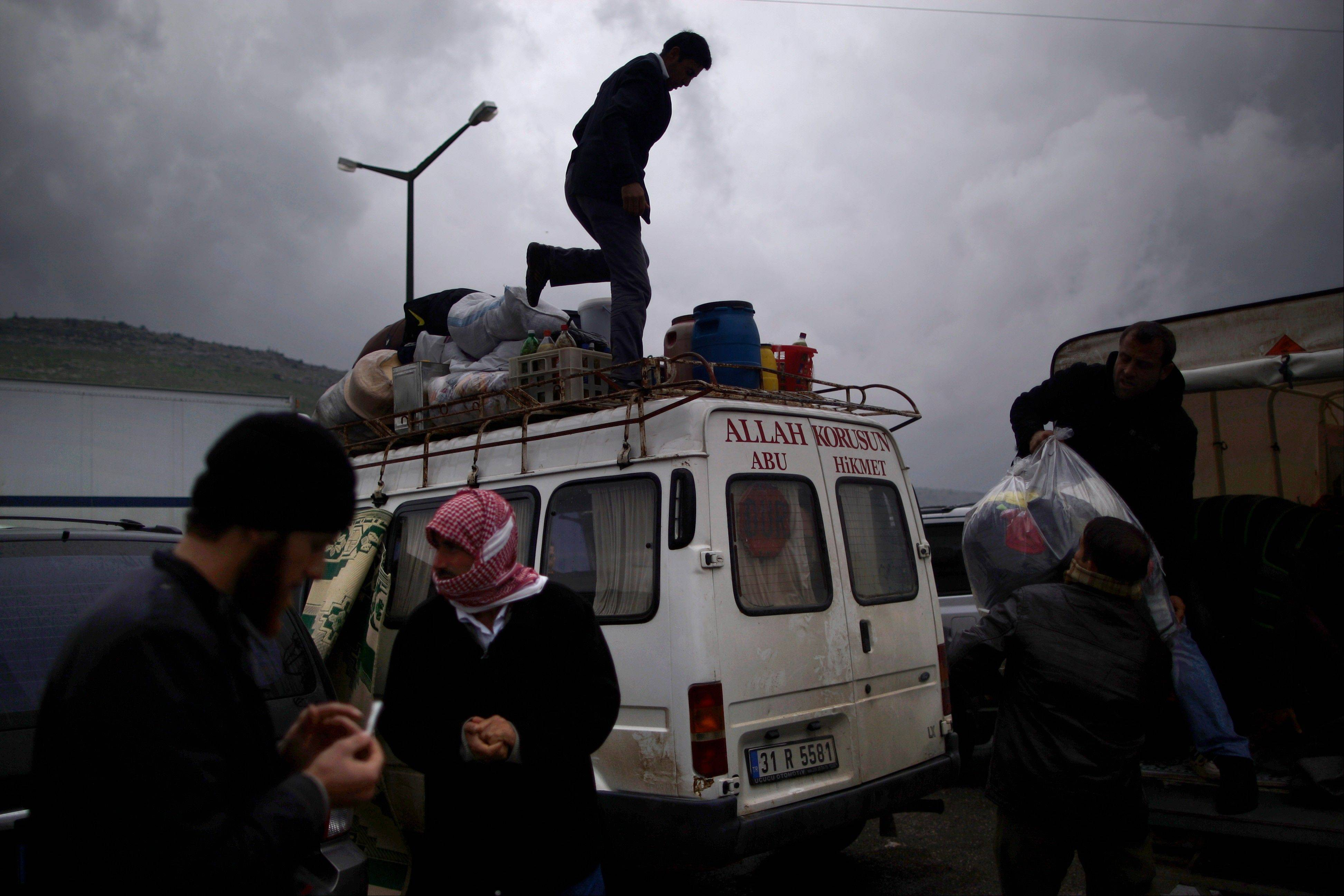 In this photo from Dec. 20, Syrian refugees, who fled their home in Idlib due to a government airstrike, load their belongings into a vehicle just after crossing the border from Syria to Turkey,