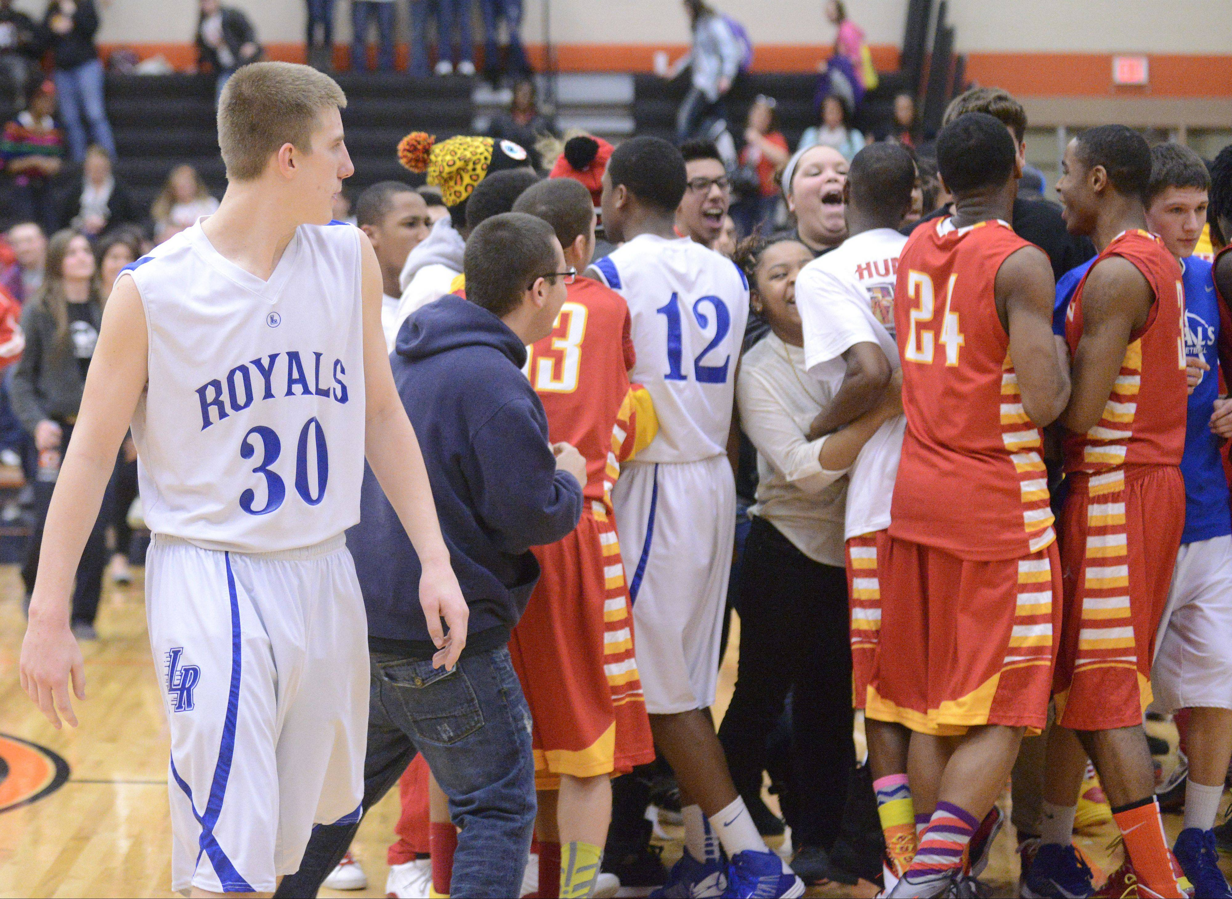 Larkin�s Brayden Royse (30) walks among celebrating teammates and fans from Rockford Jefferson, as his own teammate, Hannibal Marshall, 12, gets caught up in the crowd, after the Royals� loss to the J-Hawks in the Class 4A DeKalb sectional semifinals on Wednesday.