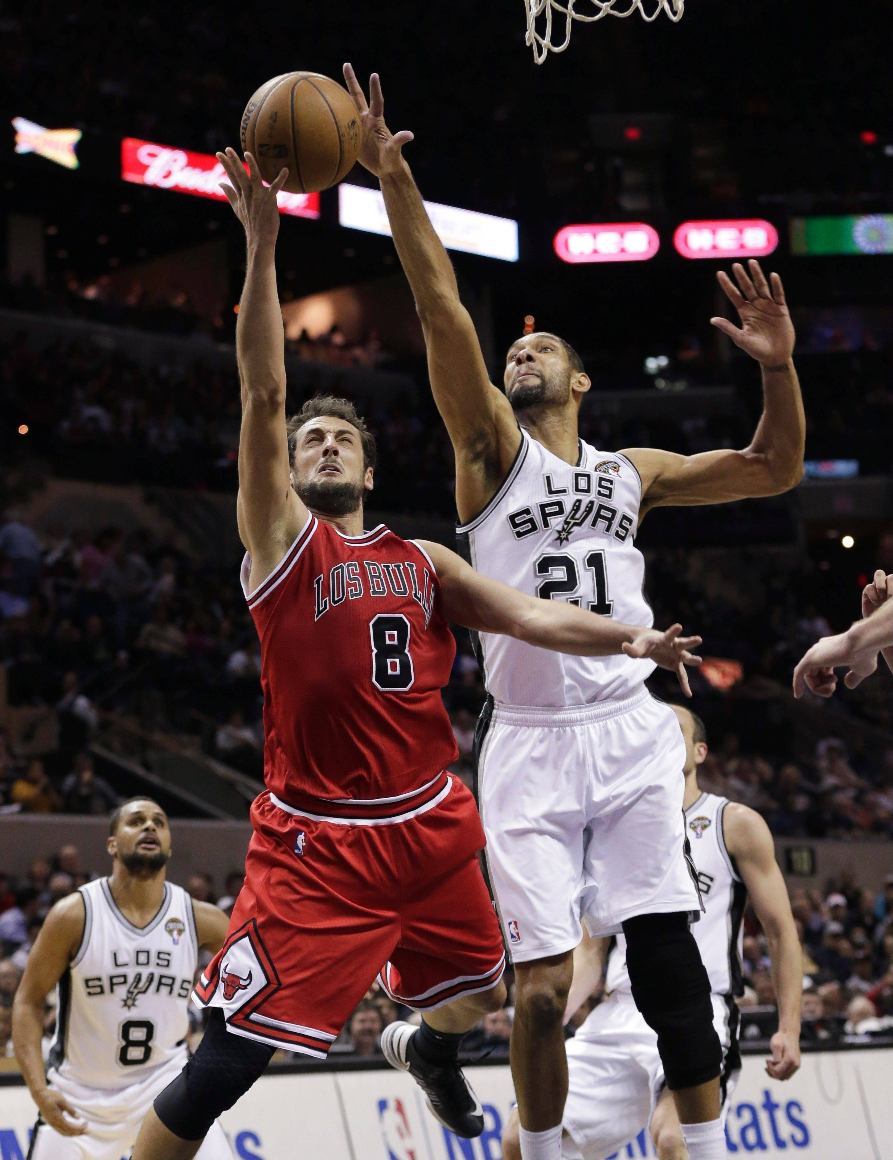 Chicago Bulls' Marco Belinelli (8) drives to the basket past San Antonio Spurs' Tim Duncan (21) during the second half of an NBA basketball game on Wednesday, March 6, 2013, in San Antonio. San Antonio won 101-83. (AP Photo/Eric Gay)