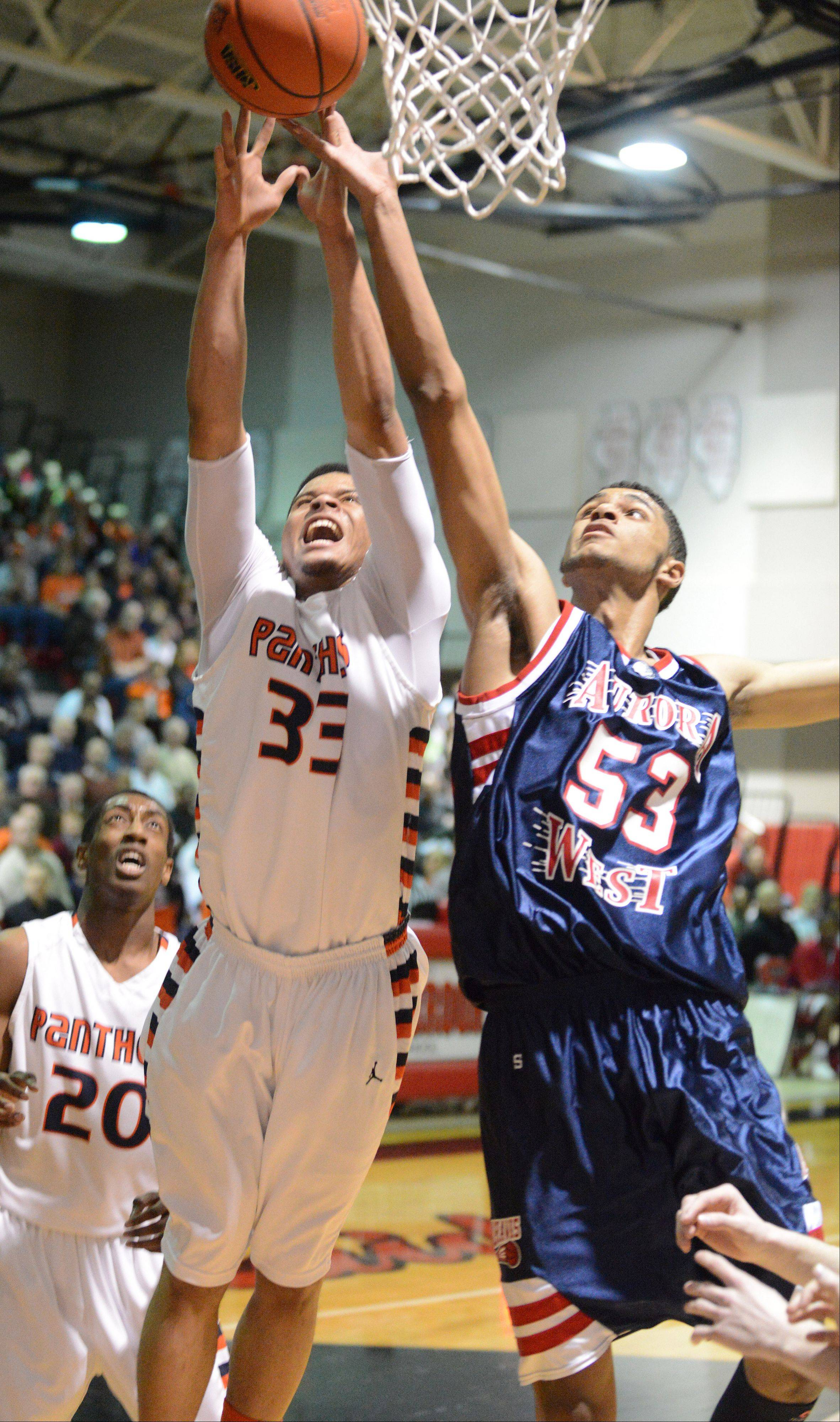 Darion Reddick of Oswego,left, and Joshua Mcauley of West Aurora go for a rebound.