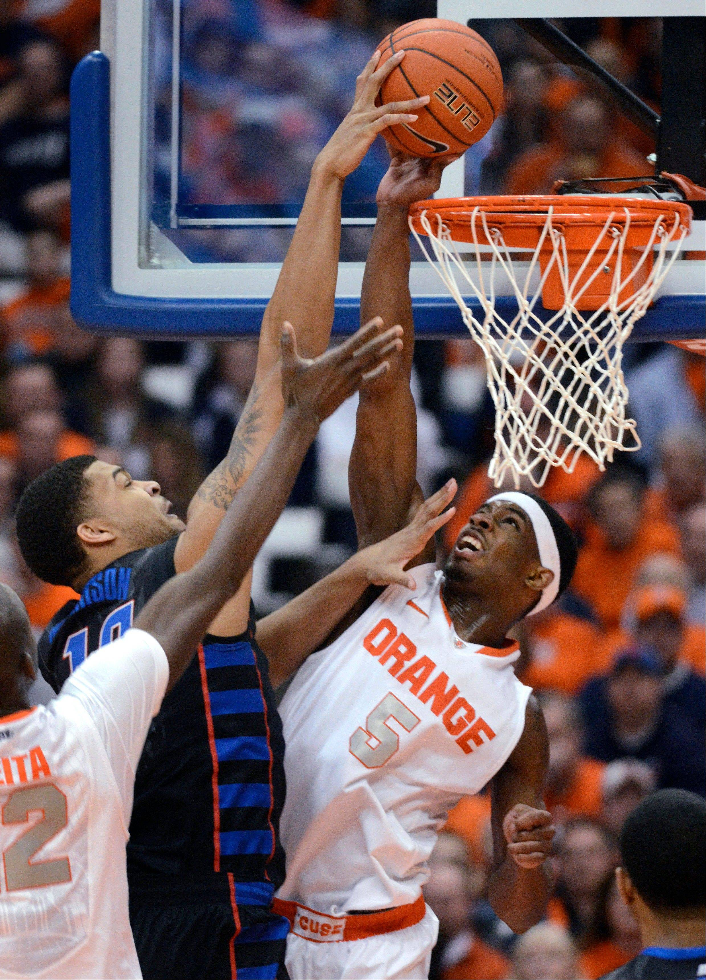 Syracuse's C.J. Fair stops DePaul's Derrell Robertson from scoring during the second half in an NCAA college basketball game in Syracuse, N.Y., Wednesday, March 6, 2013. Syracuse won 78-57. (AP Photo/Kevin Rivoli)