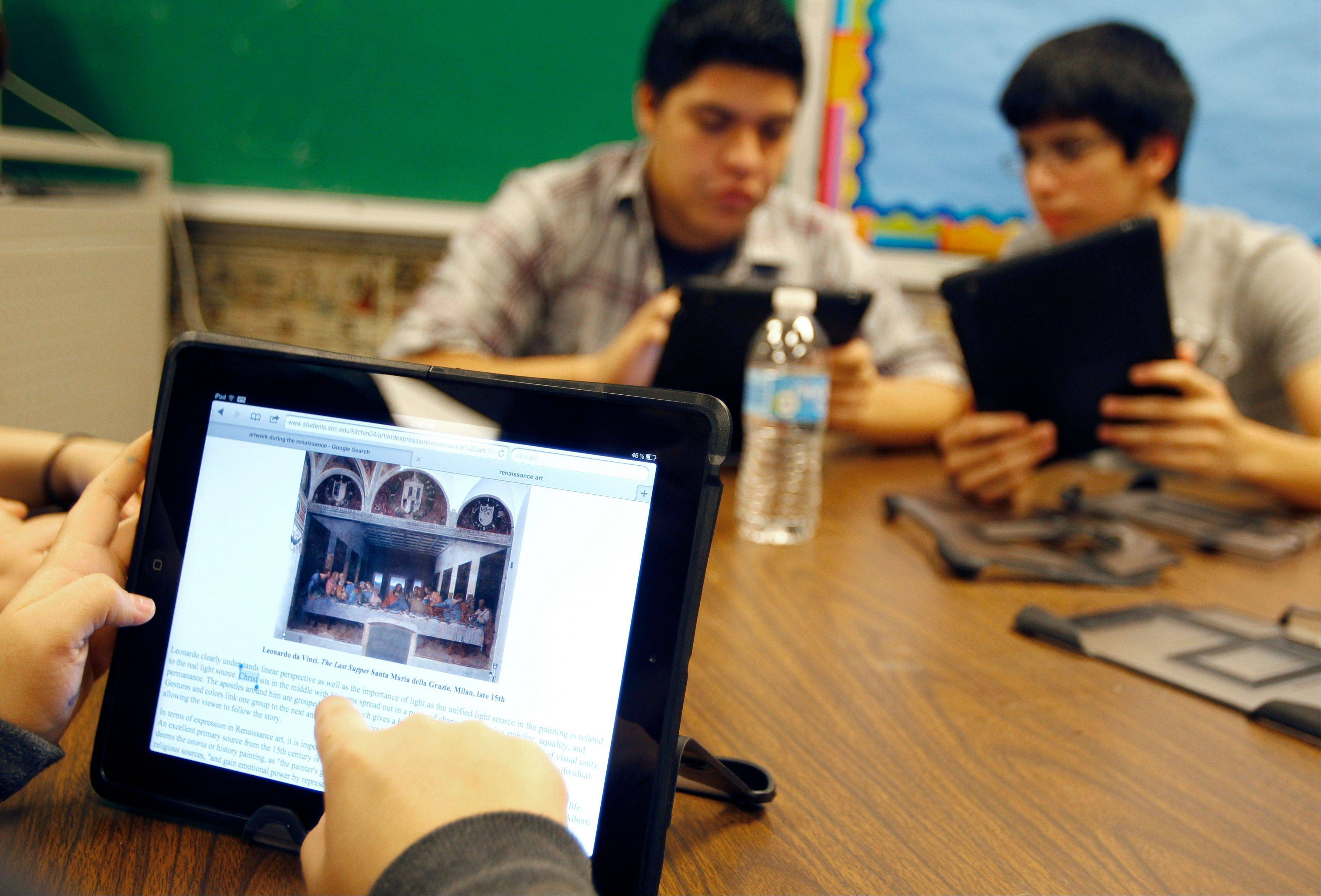 "Ysabella Ortegon, 16, reads about Leonardo da Vinci's painting ""The Last Supper,"" while working on her new iPad at McAllen Memorial High School in McAllen, Texas."