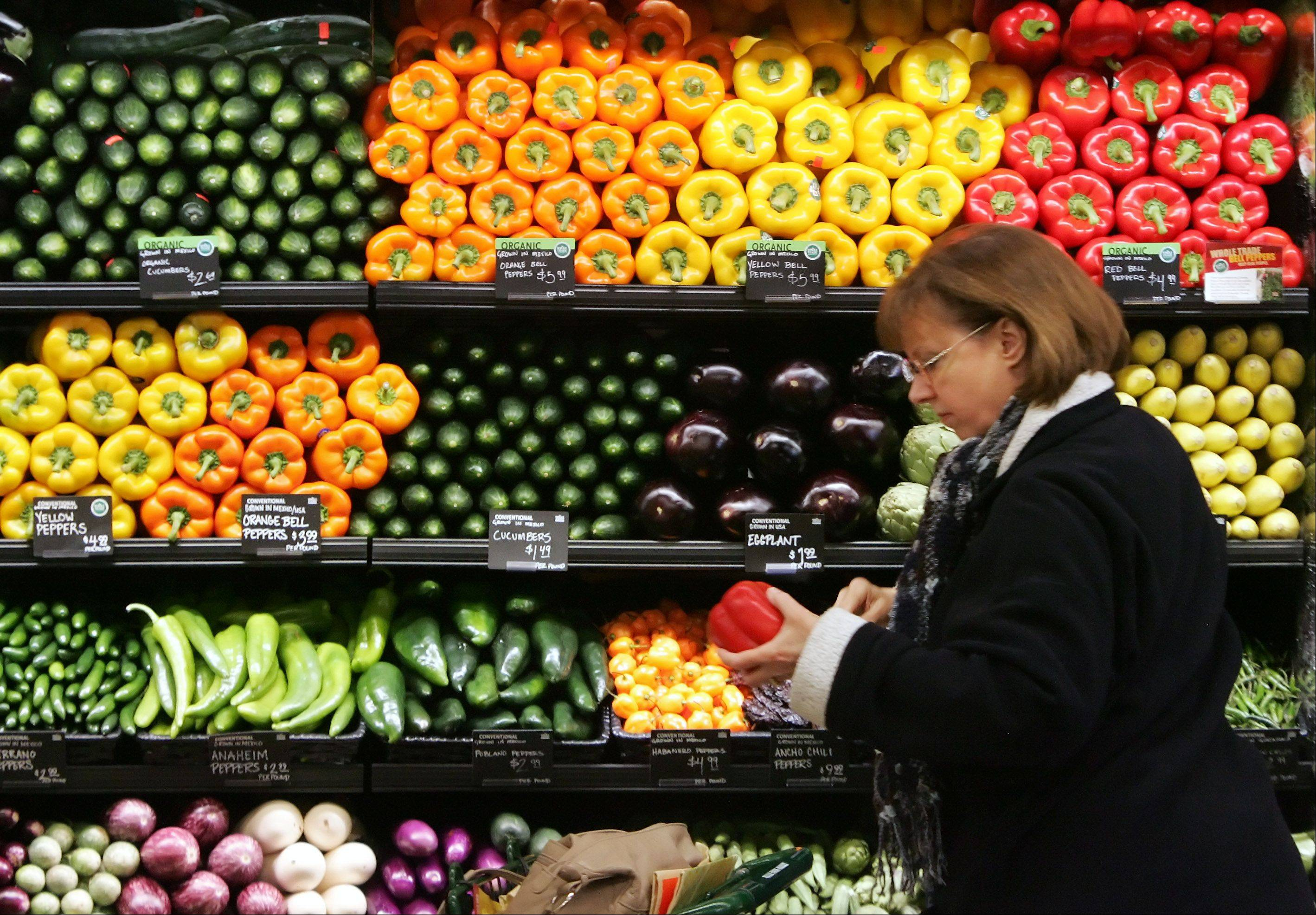 Elaine Cotter, of Long Grove, looks at an organic red pepper during the grand opening of the Whole Foods store Wednesday in Kildeer. The store has relocated from a facility in Palatine.