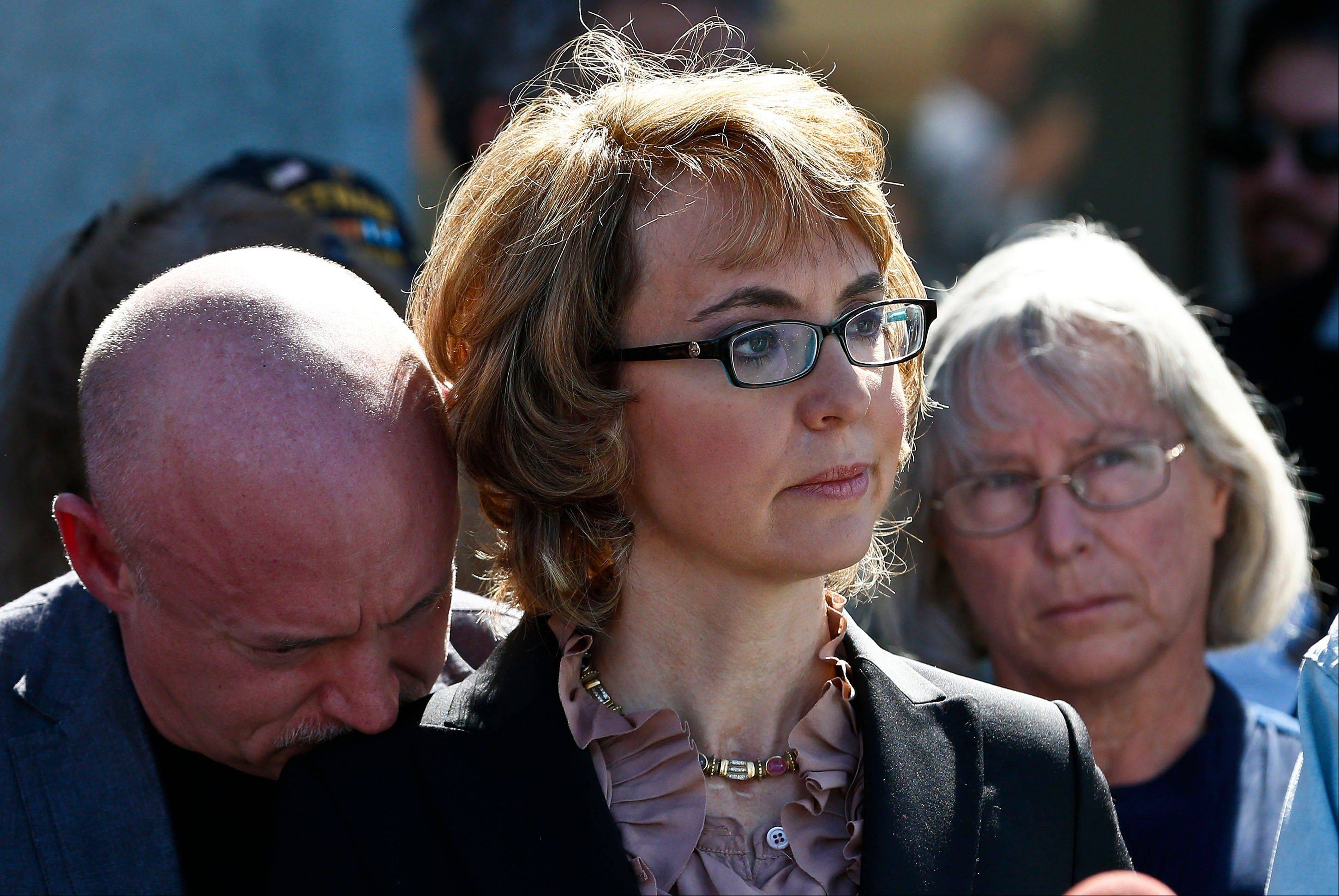 Former Rep. Gabrielle Giffords, center, is joined by her husband Mark Kelly, left, and Emily Nottingham, mother of shooting victim Gabe Zimmerman, listening to a speaker as they returned to the site of a shooting that left her critically wounded to urge key senators to support expanded background checks for gun purchases Wednesday in Tucson, Ariz.