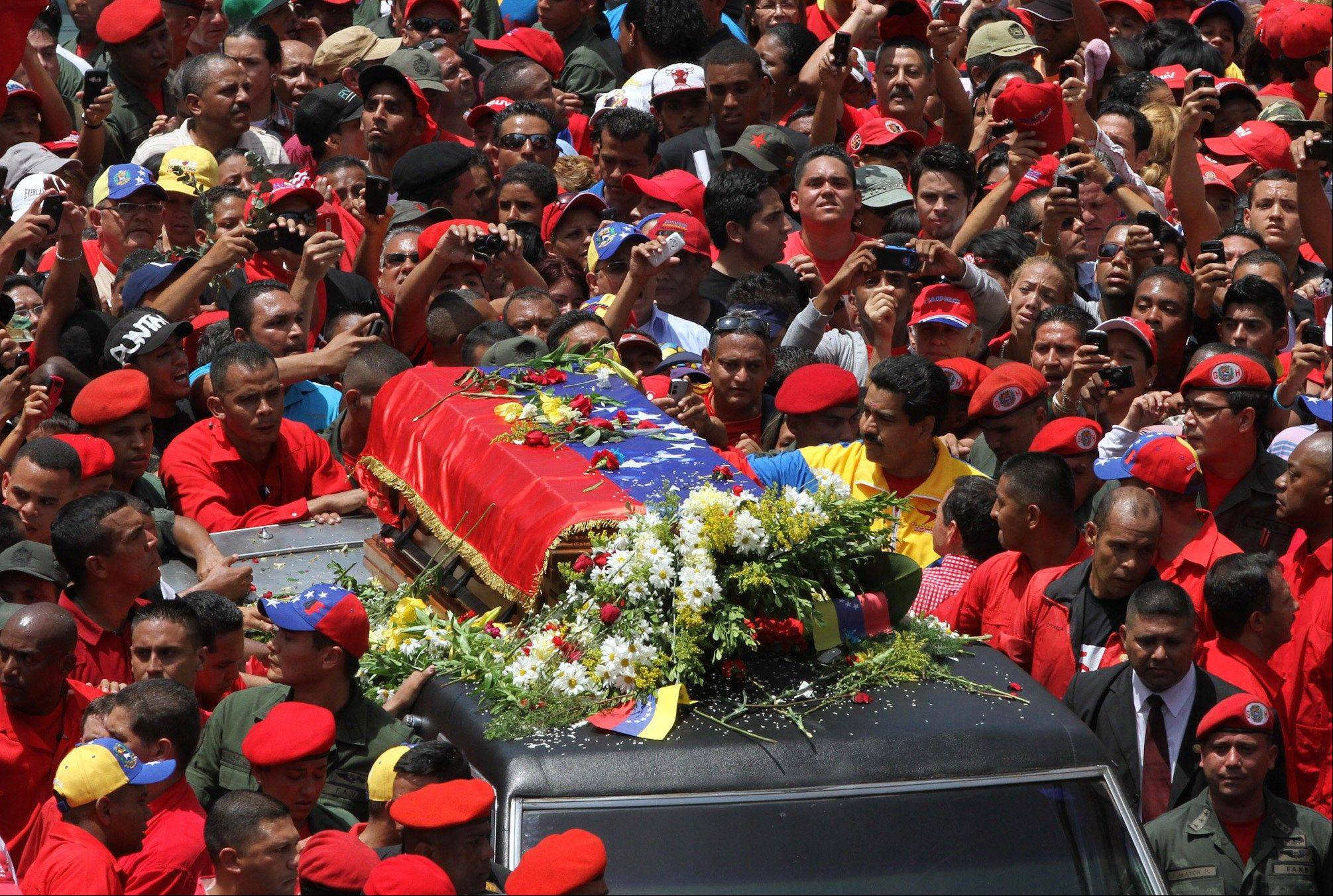 Venezuela's Vice President Nicolas Maduro walks alongside the flag-draped coffin carrying the remains of the late President Hugo Chavez, along with other supporters, as it is paraded from the hospital where he died Tuesday to a military academy where his body will lie in state in Caracas, Venezuela, Wednesday.