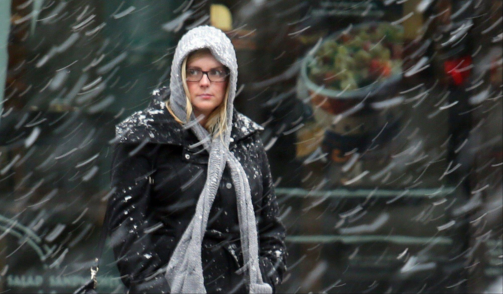 A morning commuter, bundled against the cold, watches the snow begin to fall in Washington early Wednesday.