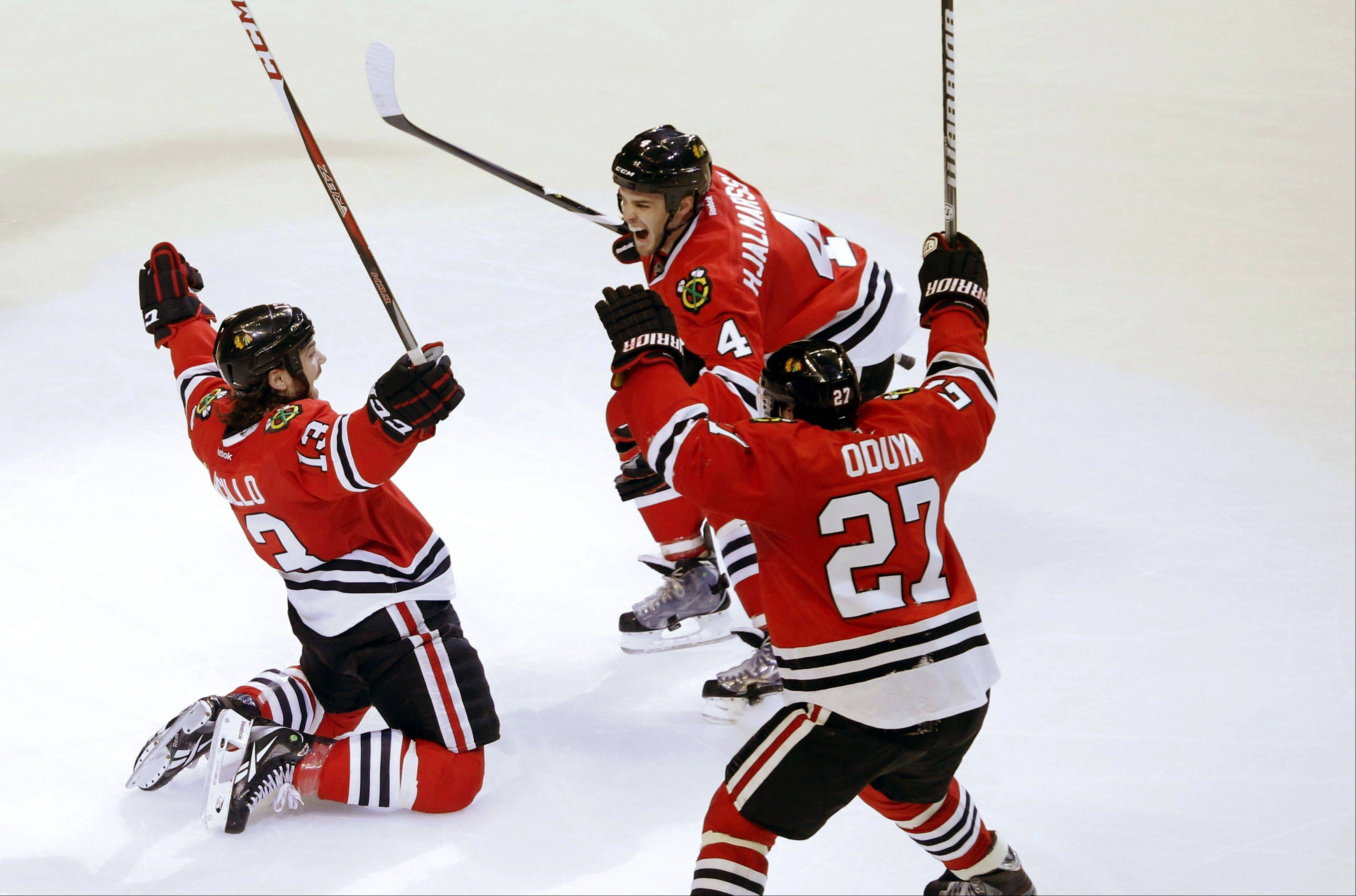 Chicago Blackhawks left wing Daniel Carcillo, left, celebrates his winning goal with Niklas Hjalmarsson and Johnny Oduya .