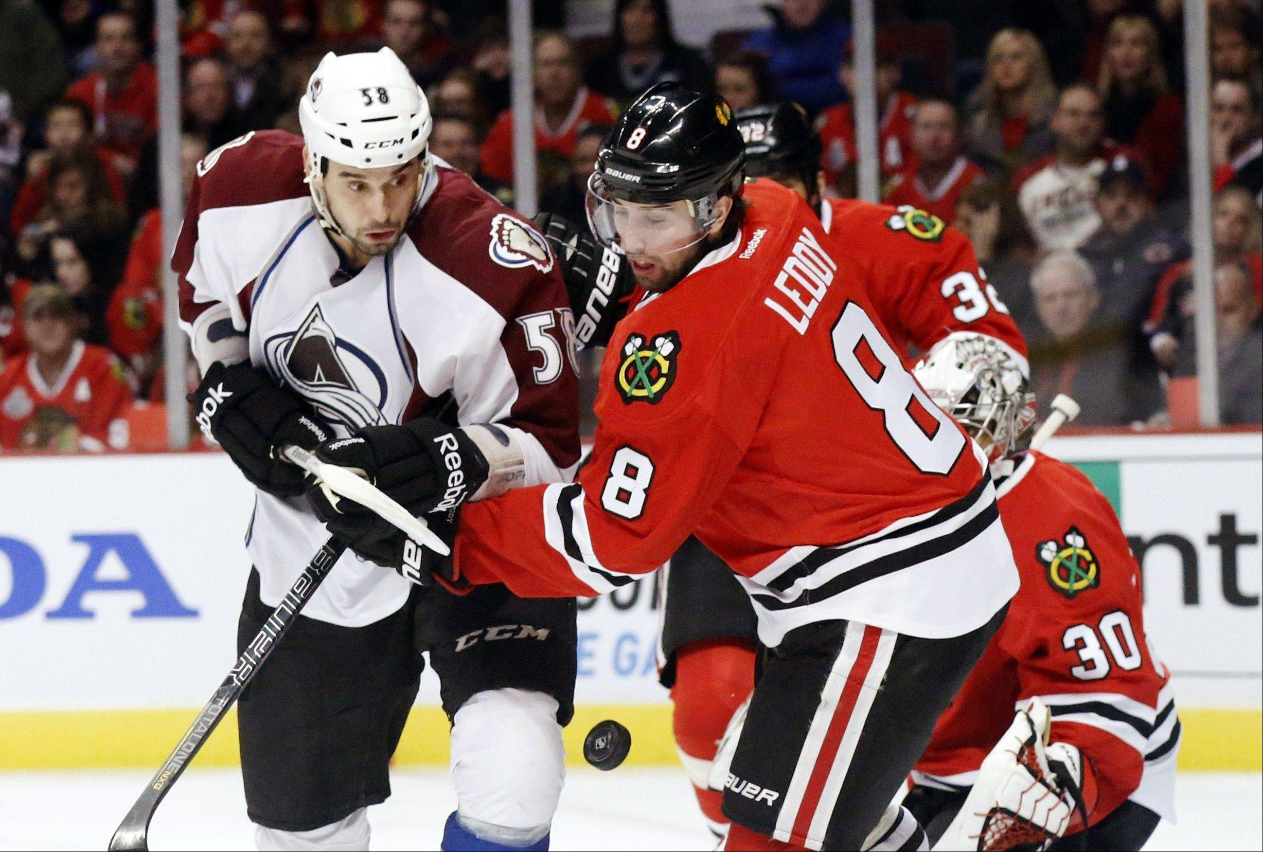 Chicago Blackhawks defenseman Nick Leddy and Colorado Avalanche left wing Patrick Bordeleau battle for a loose puck during the first period.