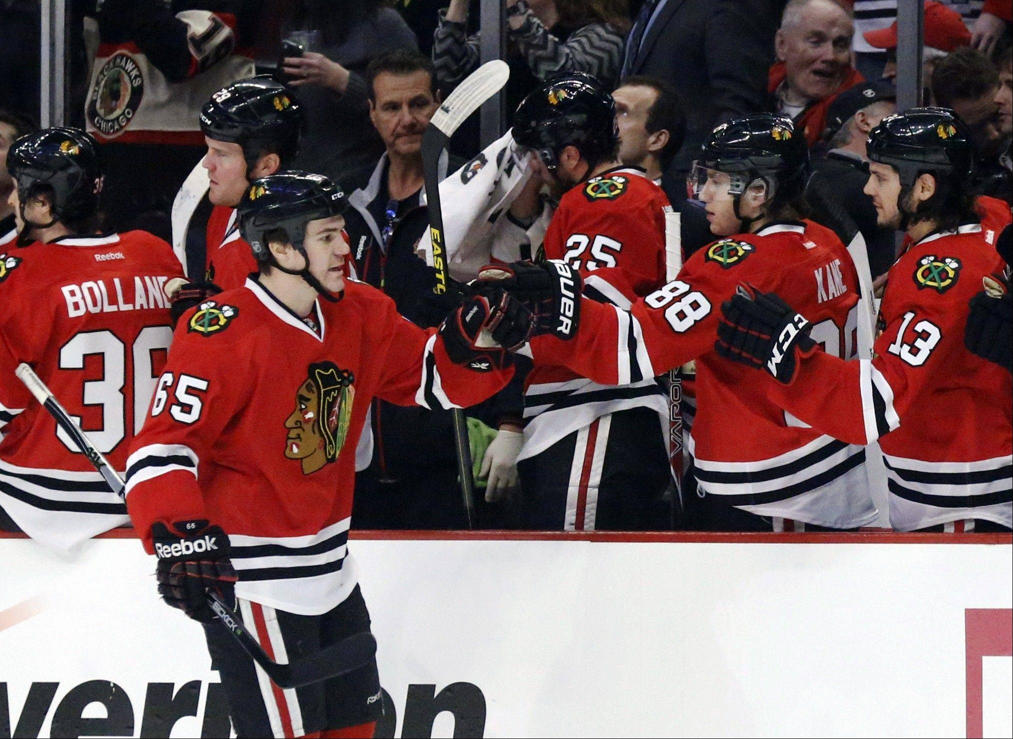 Chicago Blackhawks center Andrew Shaw celebrates his goal with teammates during the first period .