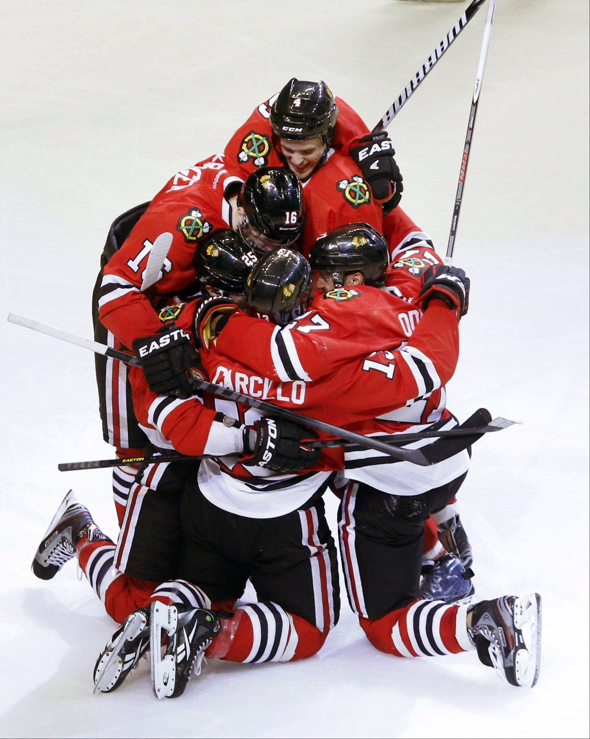 Chicago Blackhawks left wing Daniel Carcillo, bottom center, is mobbed by teammates as they celebrate Carcillo's winning goal during the third period of an NHL hockey game against the Colorado Avalanche, Wednesday, March 6, 2013, in Chicago. The Blackhawks won 3-2.