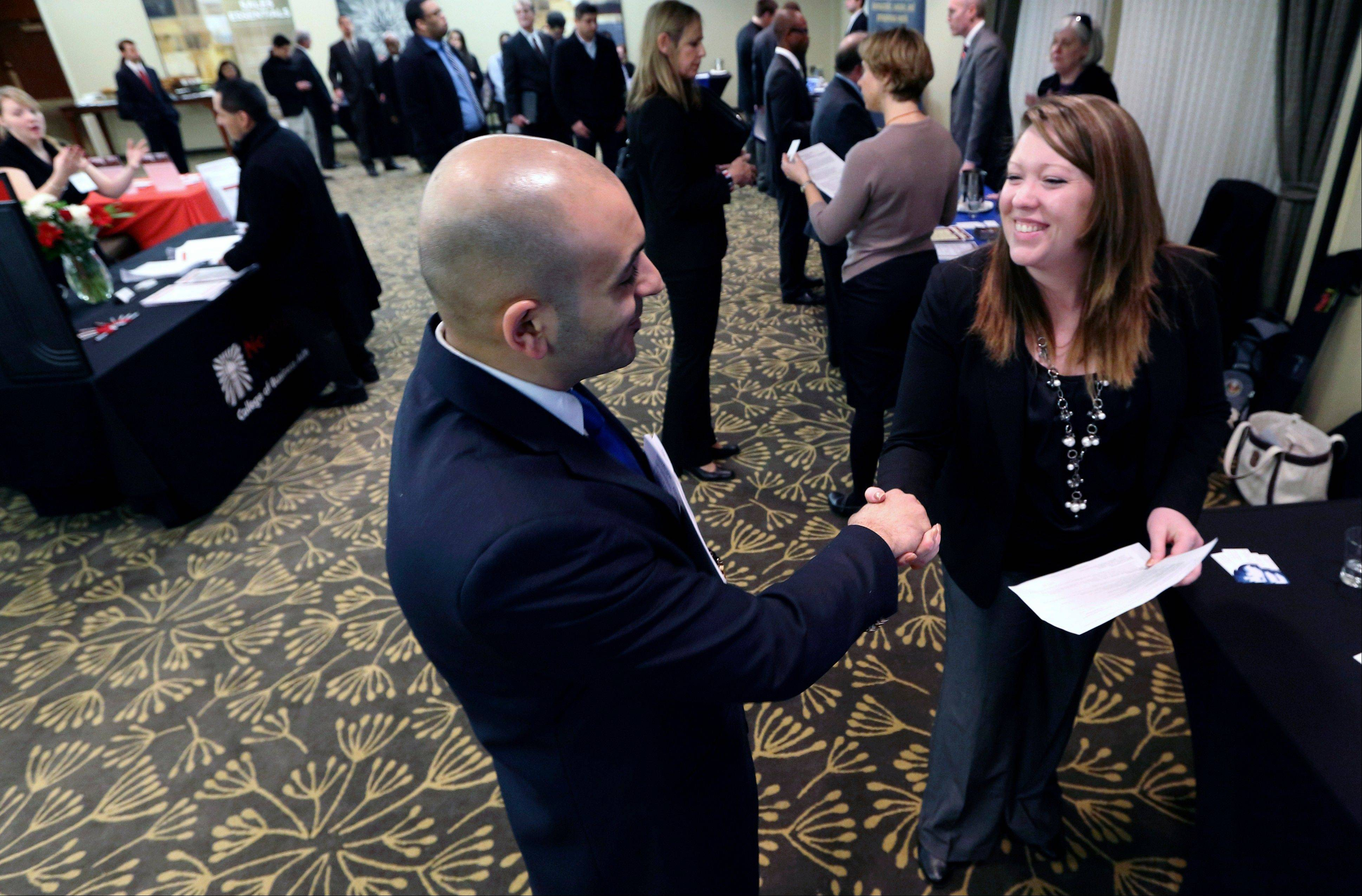 Sayed Mouawad, left, of Providence, R.I., shakes hands with Jillian Wallace of Matix, Inc., during a job fair in Boston. The number of people seeking U.S. unemployment aid fell to a seasonally adjusted 340,000 in the week ended March 2, driving down the four-week average to its lowest level in five years.