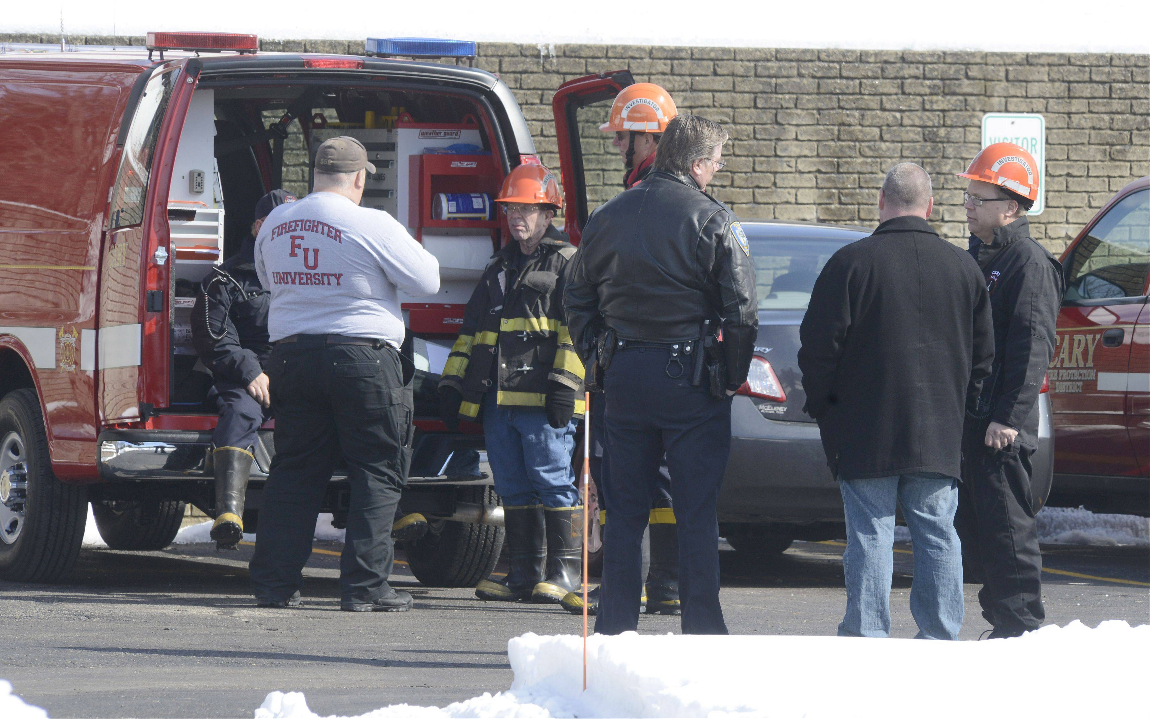 Cary Fire Department investigators and a Cary police officers gather in the parking lot of Fox Valley Systems in Cary on Thursday, the day after multiple explosions.