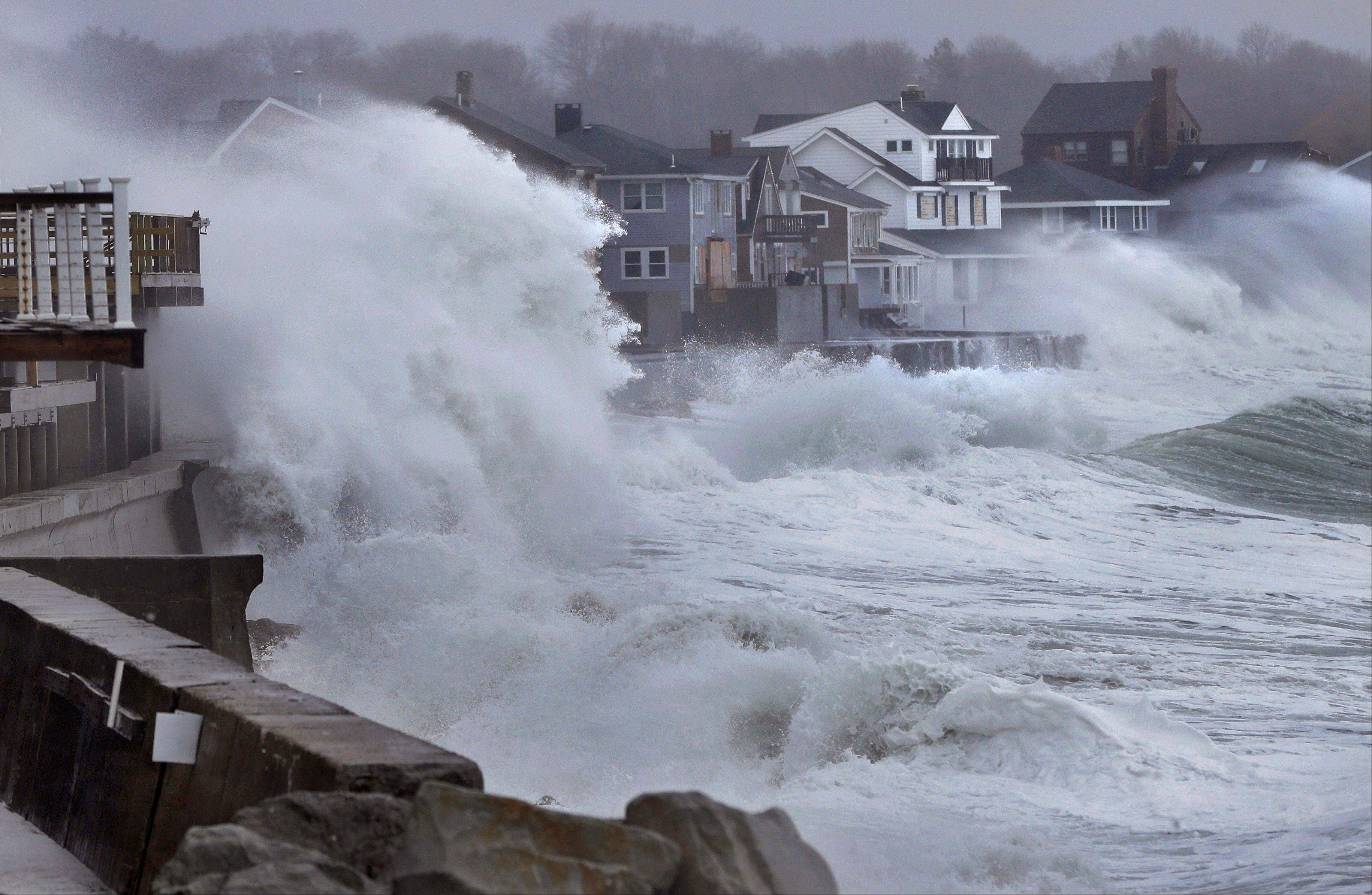 Ocean waves crash over a sea wall and into houses along the coast in Scituate, Mass., Thursday, March 7, 2013. A winter storm brought strong winds to coastal areas in the state.
