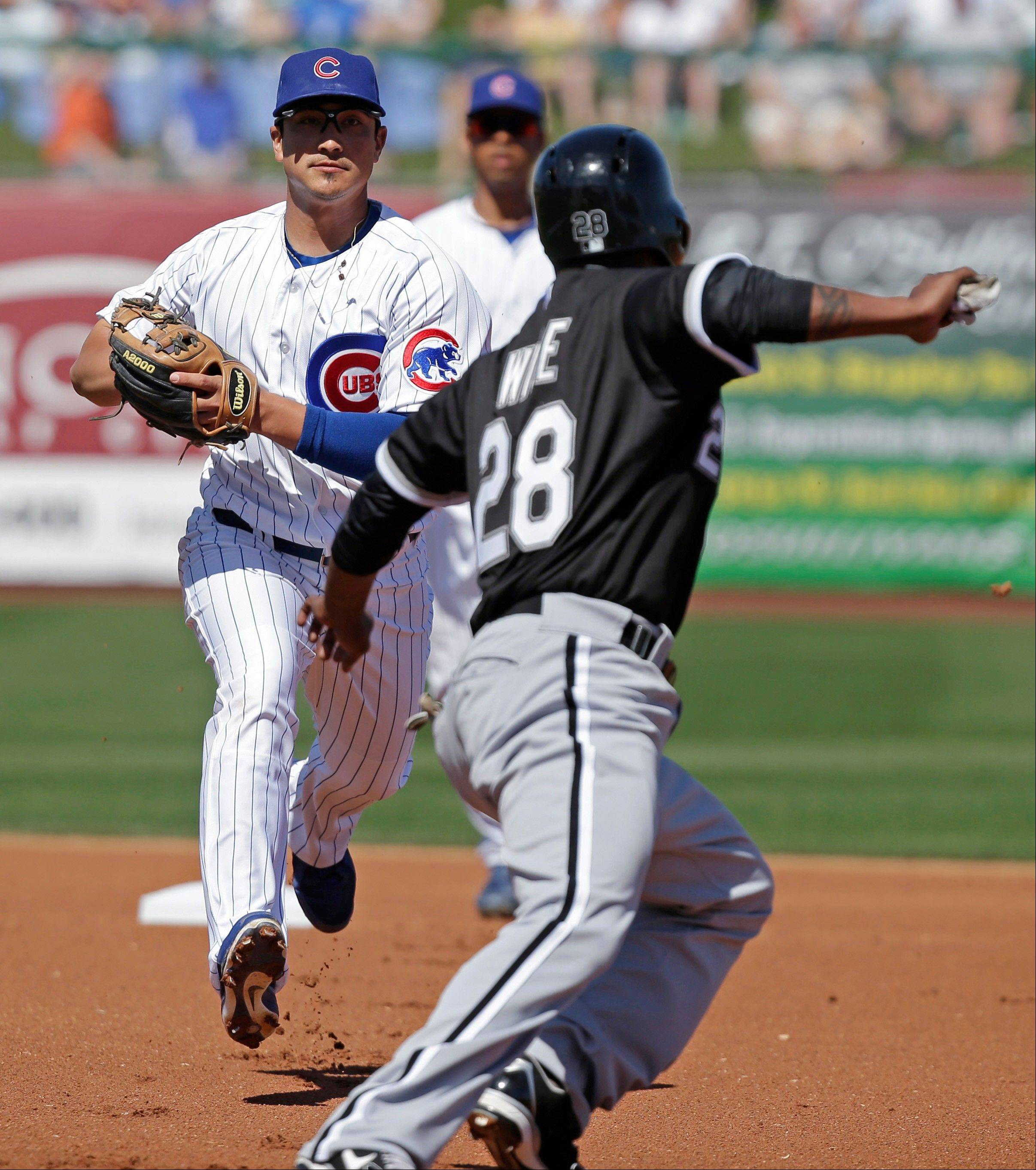 Chicago White Sox's Dewayne Wise (28) is caught is caught off first base as Chicago Cubs' Darwin Barney closes in during the first inning of a spring training baseball game Thursday, March 7, 2013, in Mesa, Ariz. Wise was out. (AP Photo/Morry Gash)