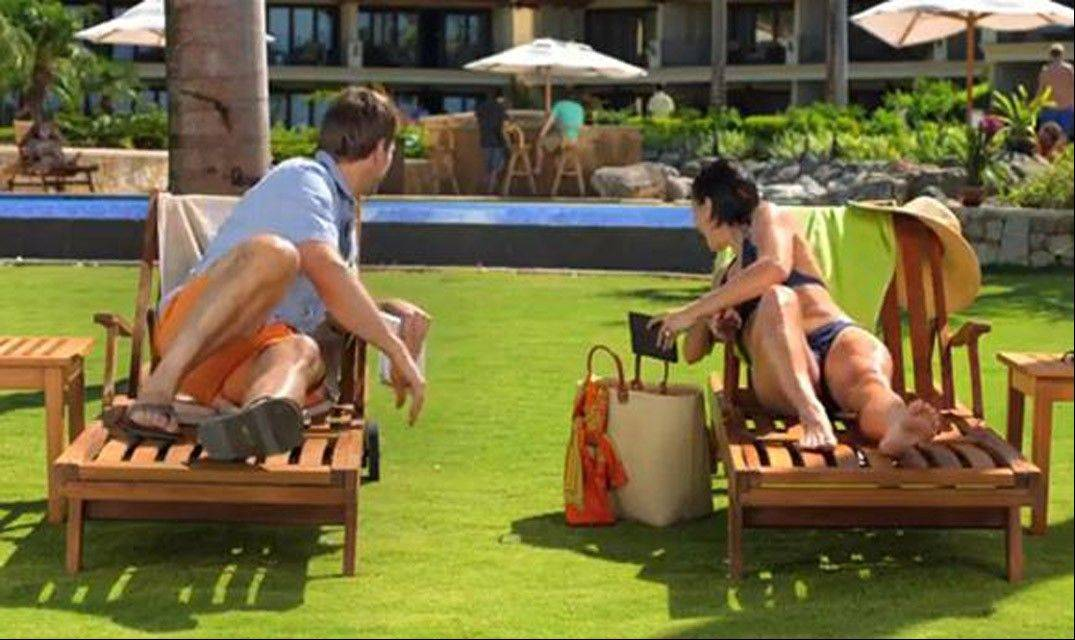 This image from video shows an image from a Kindle Paperwhite commercial featuring a young woman on a beach vacation lounging next to a young man, waiting for their husbands, shown in the background at the bar. Welcome to the latest in gay imagery in mainstream advertising, where LGBT people have been waiting for a larger helping of fairness and accuracy, on screen and in print.