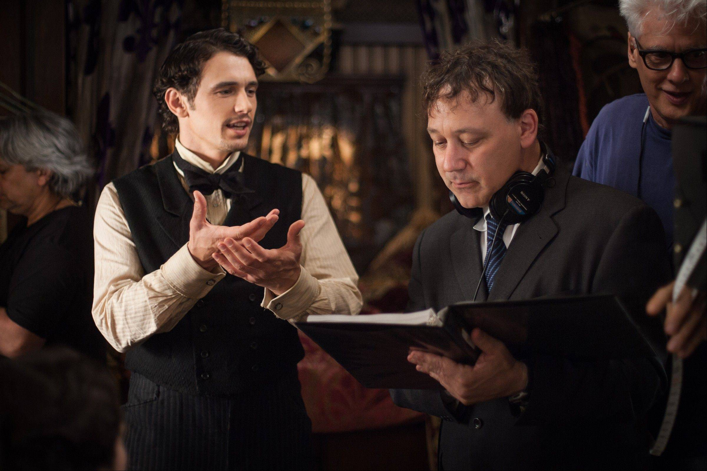 "James Franco, left, and director Sam Raimi on the set of ""Oz the Great and Powerful."" Returning to the mystical land of ""The Wizard of Oz"" apparently takes more than 70 years and hundreds of millions of dollars."