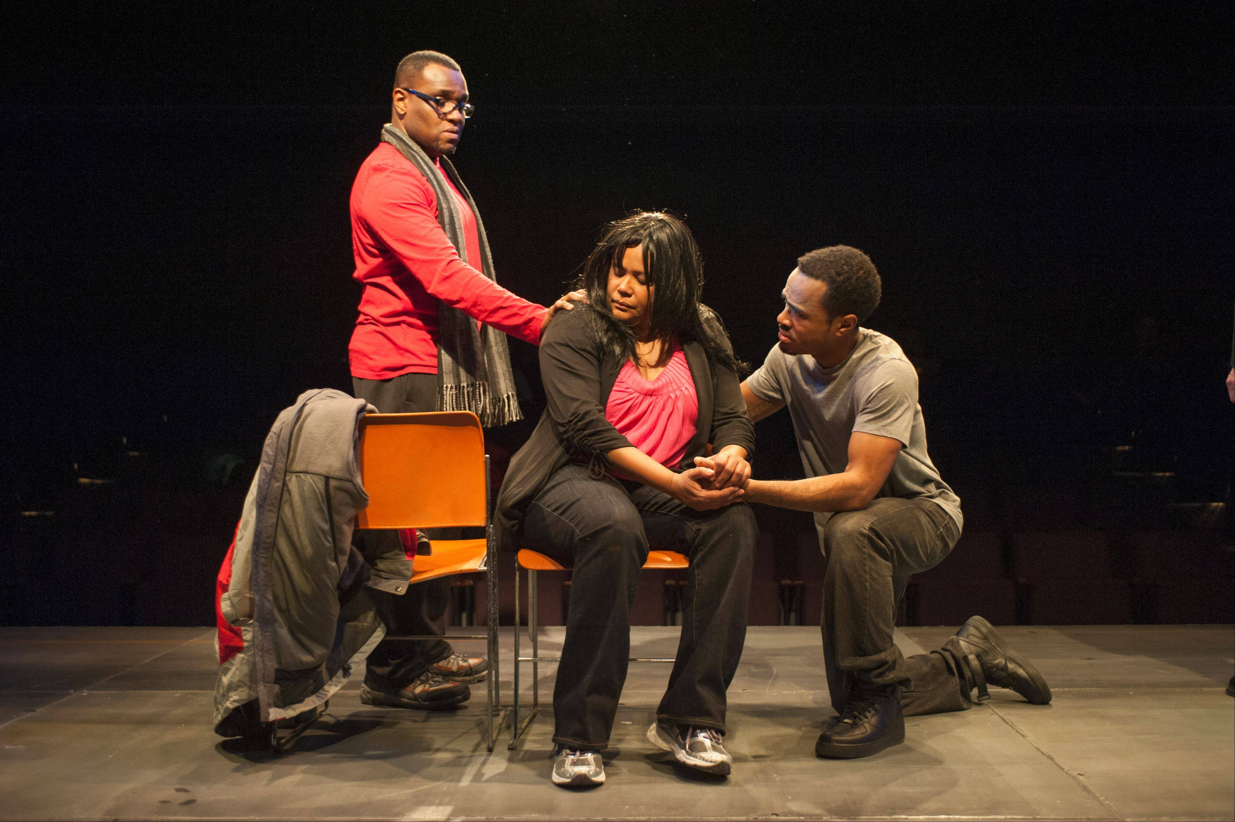 "Pastor Brooks (Mark Smith, left) comforts a grieving mother (Celeste Williams) and her son (Charles Gardner) in the Steppenwolf for Young Adults production of ""How Long Will I Cry?: Voices of Youth Violence."""